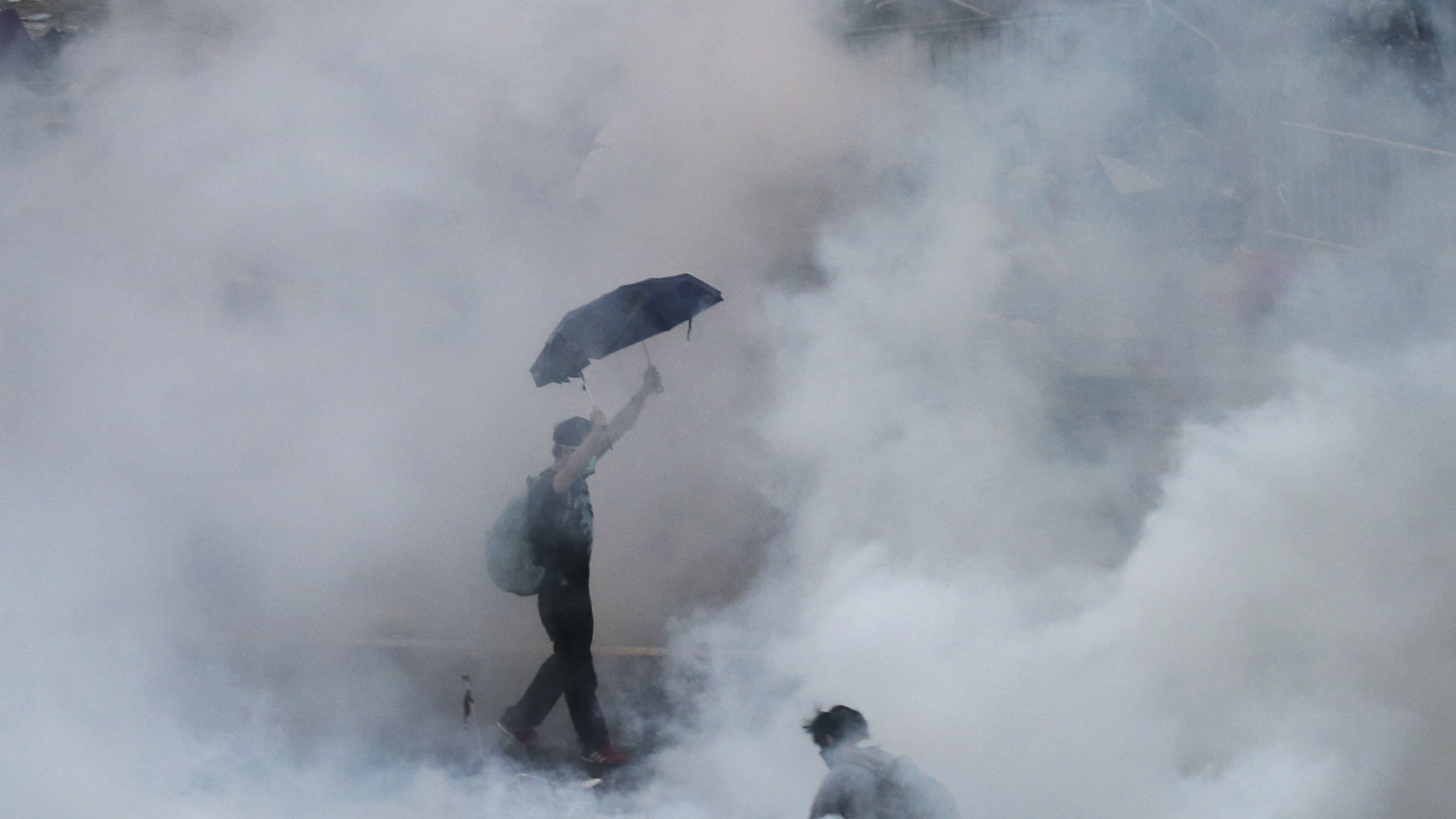 A protester walks in tear gas fired by riot policemen after thousands of protesters blocked the main street to the financial district outside government headquarters in Hong Kong on September 28, 2014.