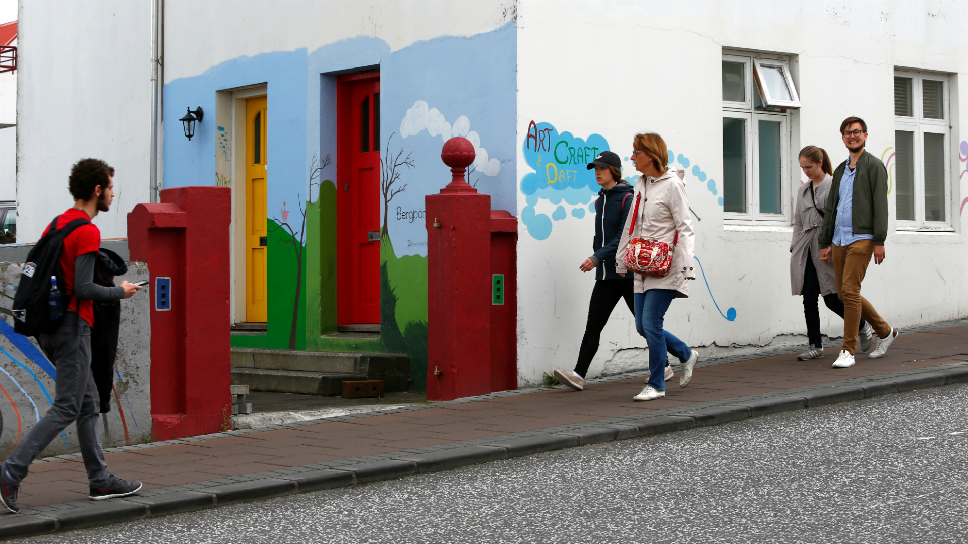 People walk pass pass a colorful house in Reykjavik, Iceland on August 4, 2017.