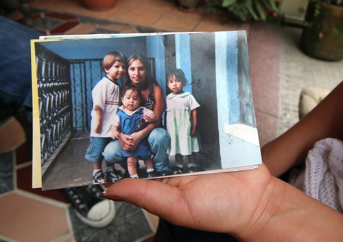 Loyda Rodríguez holding a photograph that shows her daughter Anyelí and her siblings.