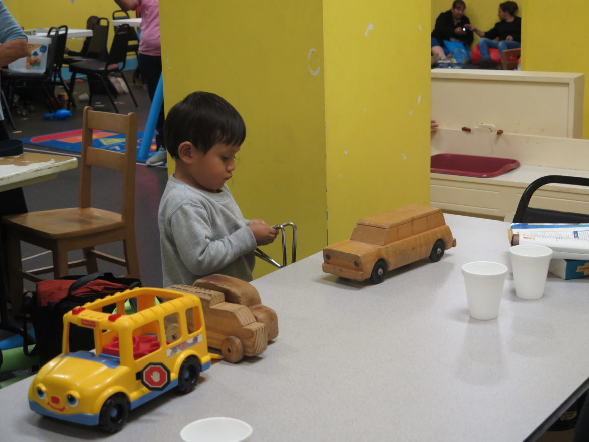 A young child takes refuge from Hurricane Harvey and plays with toys at a downtown church playroom.