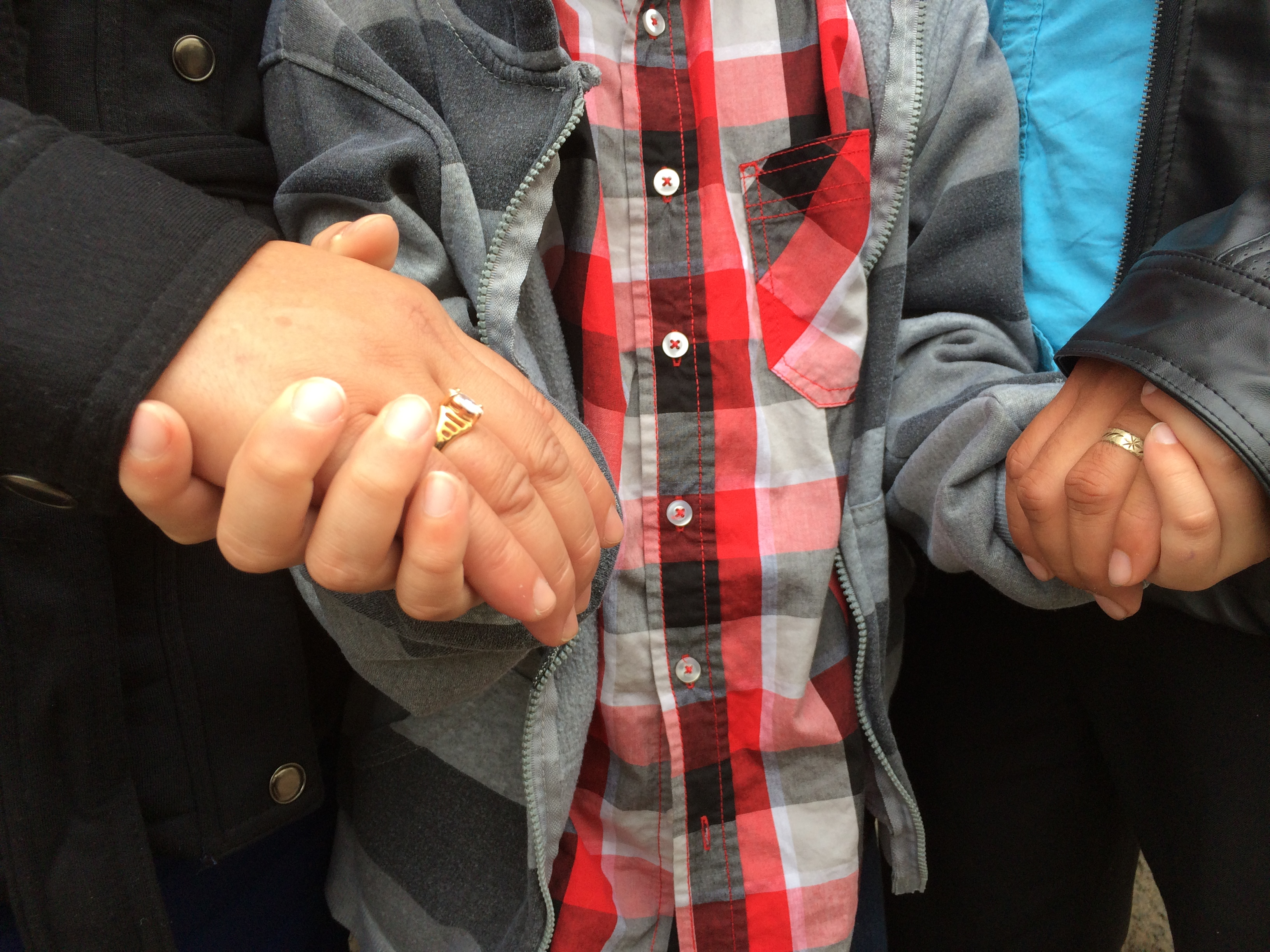 close up of three people holding hands