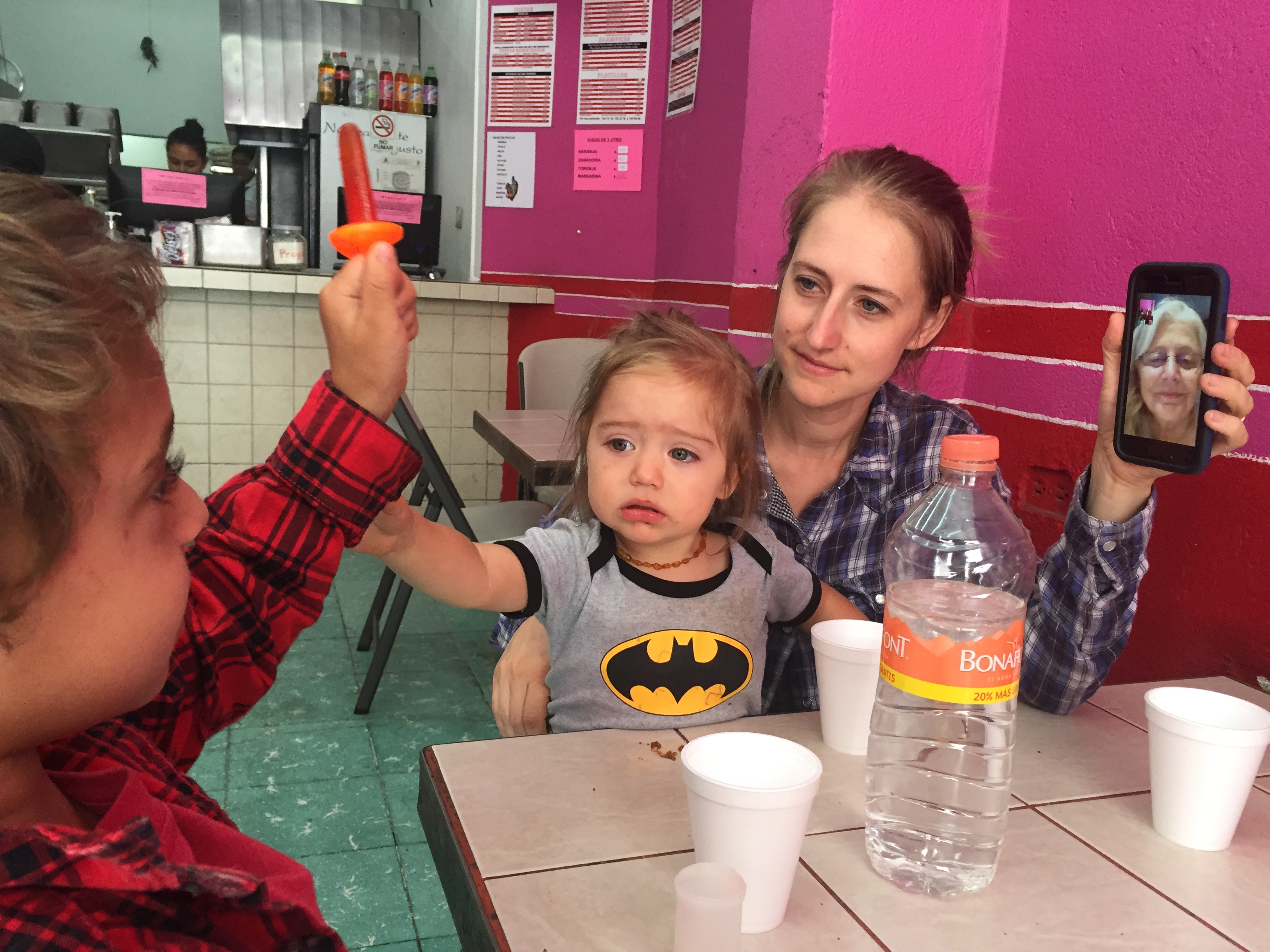 Woman sitting at table with two small children, holding up phone with another woman on video call