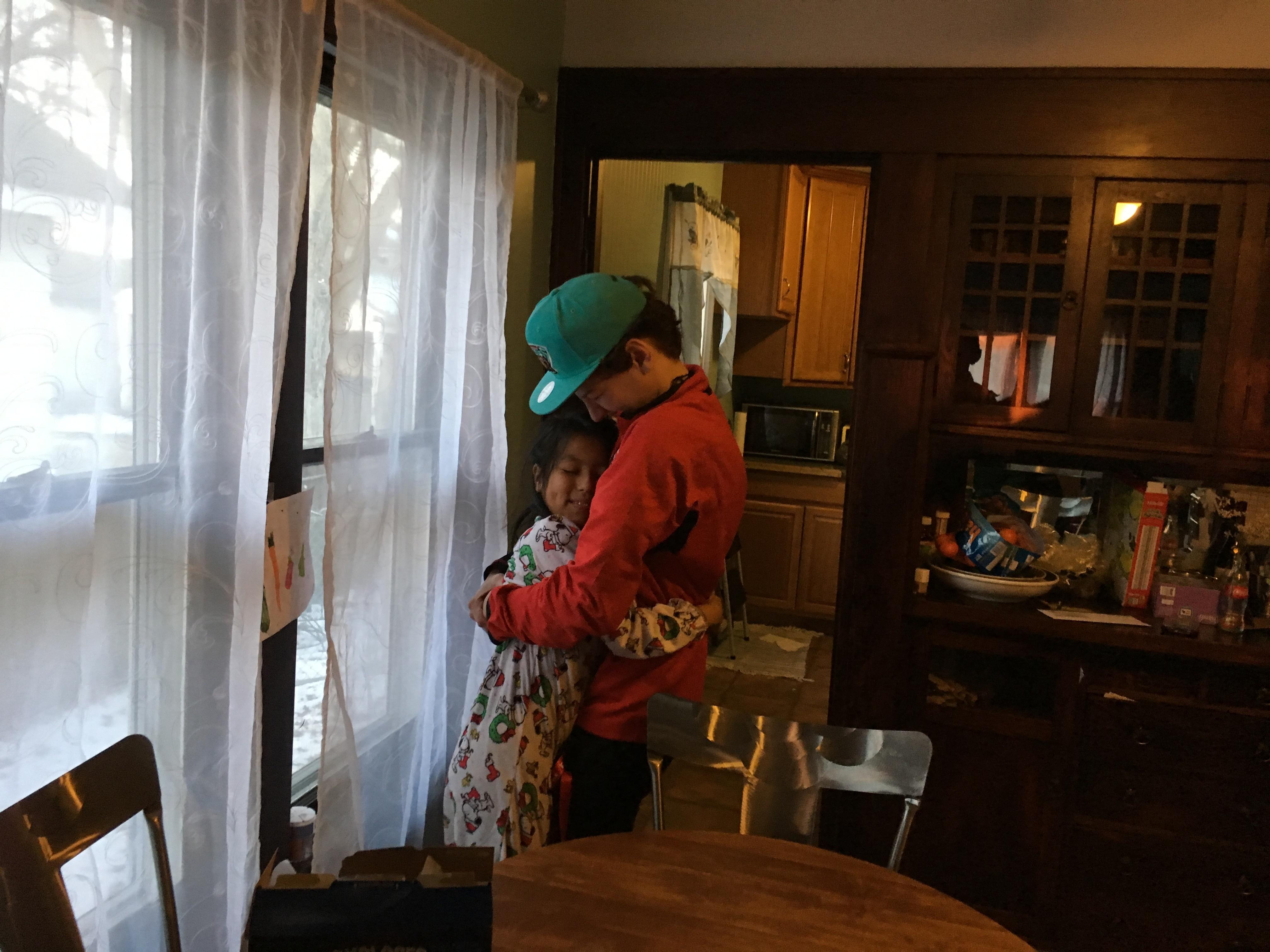Armand Melk-Johnson, 15, hugs his host sister, Mariel, goodbye.