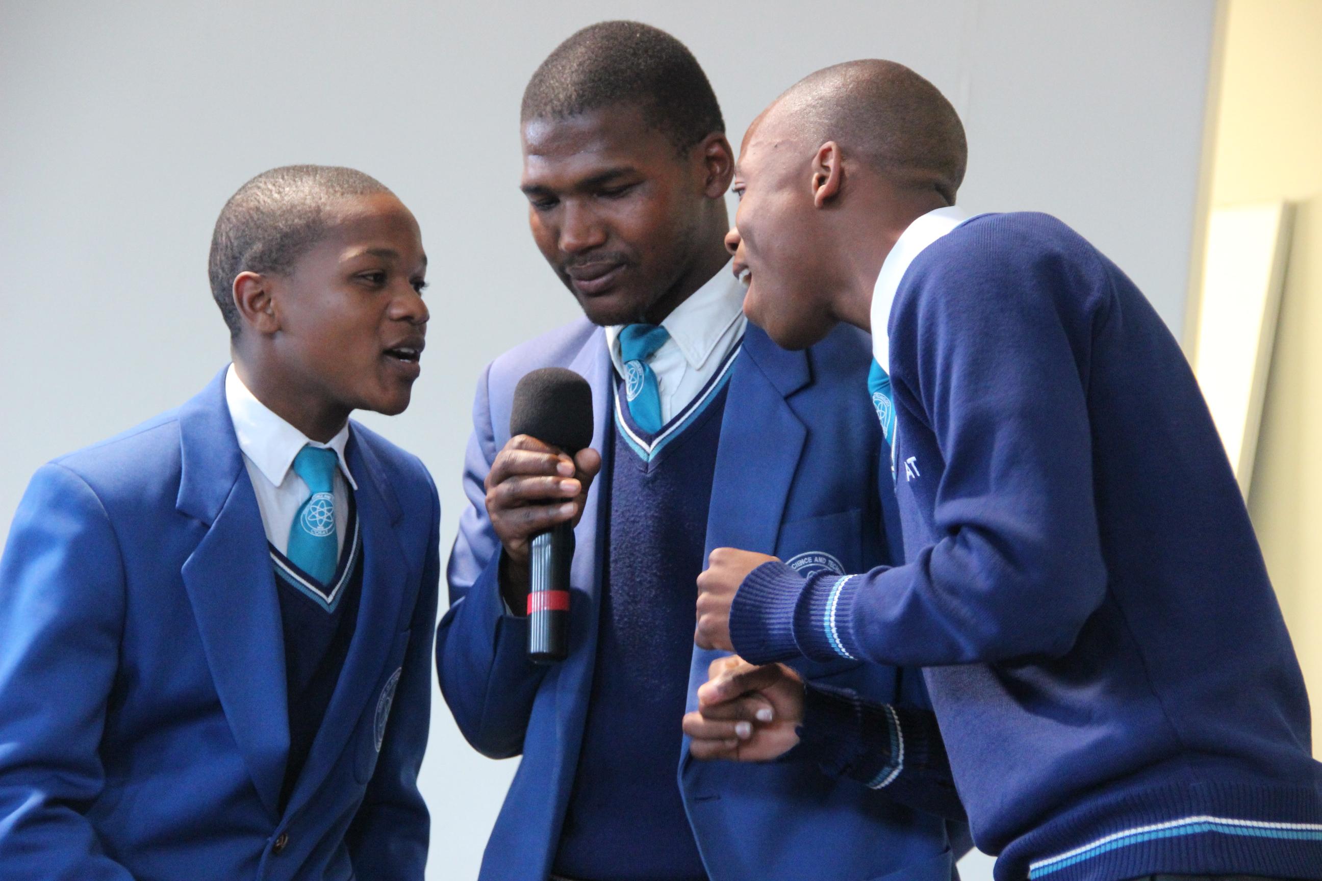 Three seniors perform a song at COSAT.