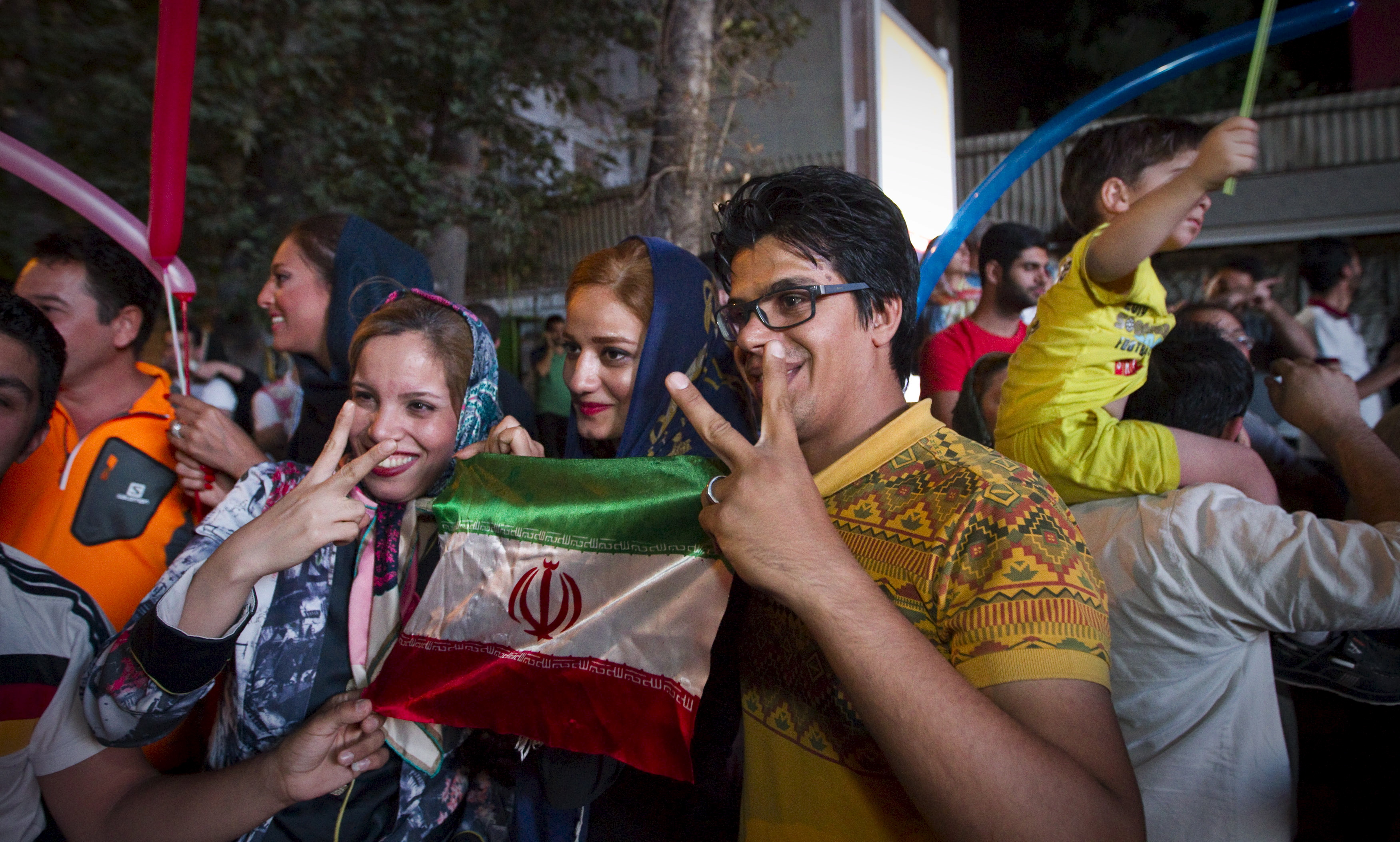 Iranians gesture as they celebrate in the streets of Tehran following the nuclear deal announced on July 14th. Iranian president Hassan Rouhani said a nuclear deal with major powers would open a new chapter of cooperation with the outside world after year