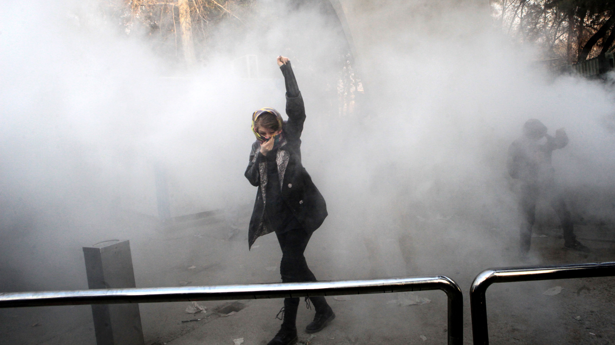 An Iranian woman raises her fist, covering her face with a scarf, as smoke surrounds her.