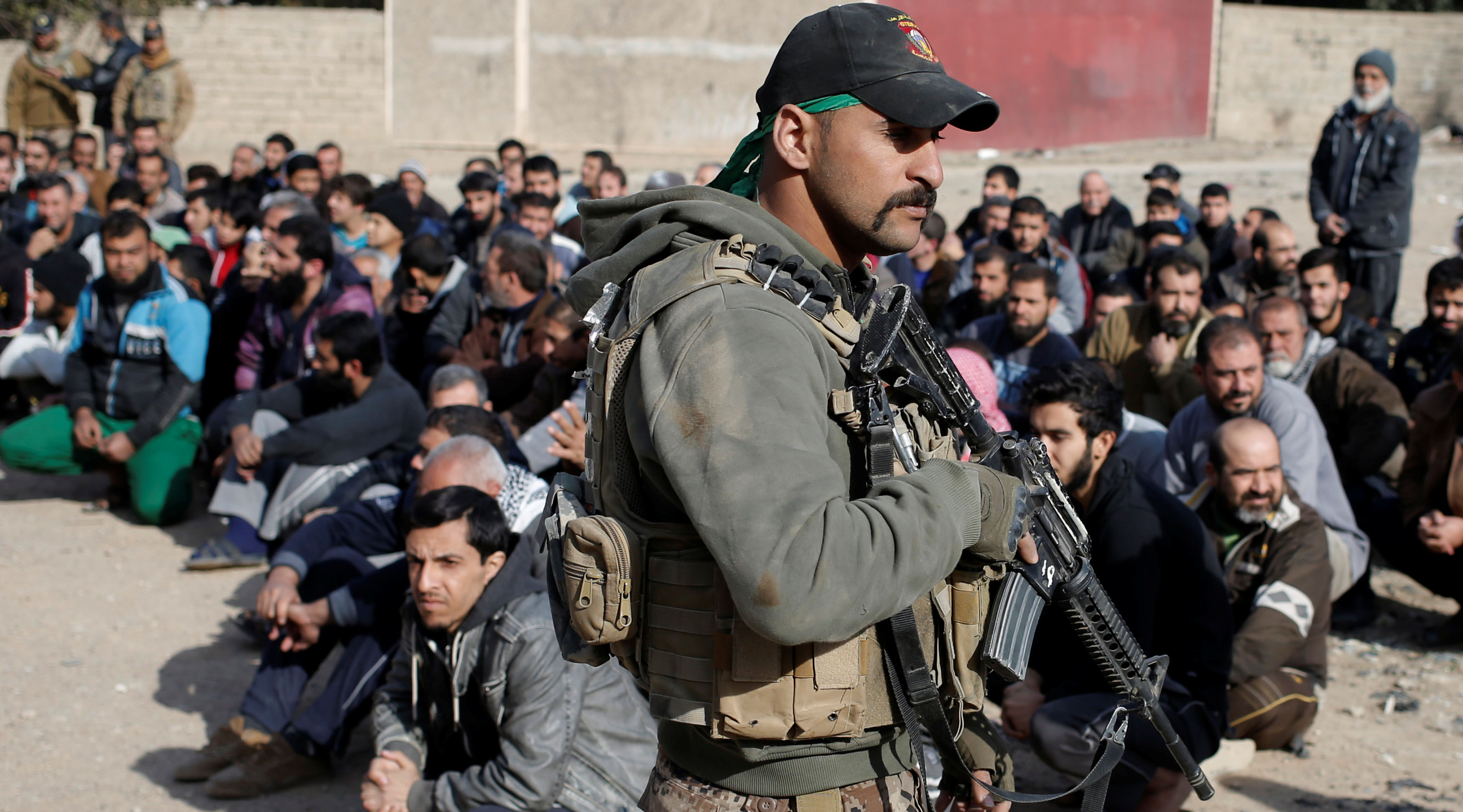 Iraqi special forces intelligence agents check men's IDs in the search for Islamic State fighters in Mosul, Iraq on Nov. 27.