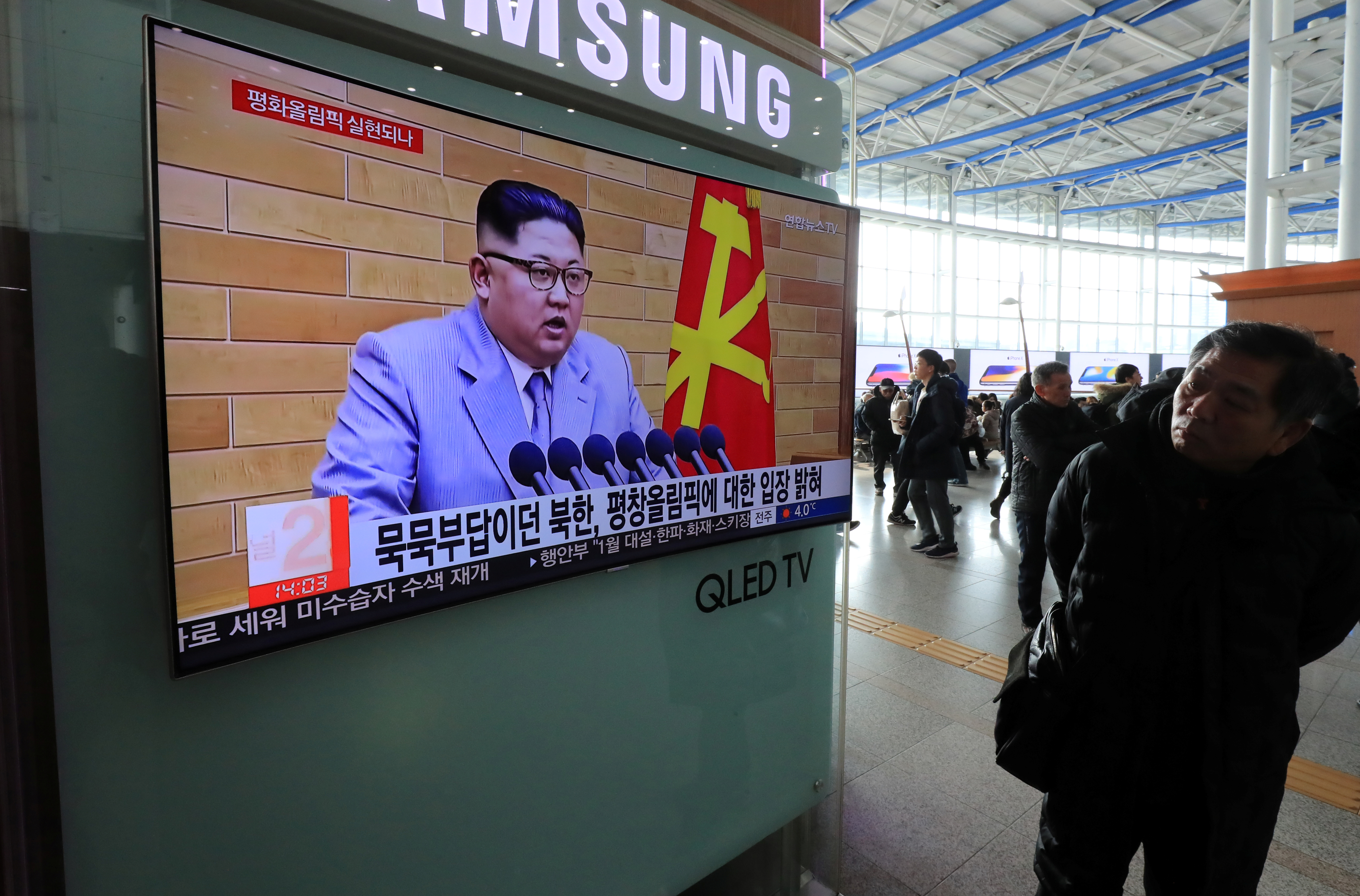 A man in Seoul, South Korea, watches a TV broadcasting a news report on North Korea's leader Kim Jong-un speaking during a New Year's Day speech.