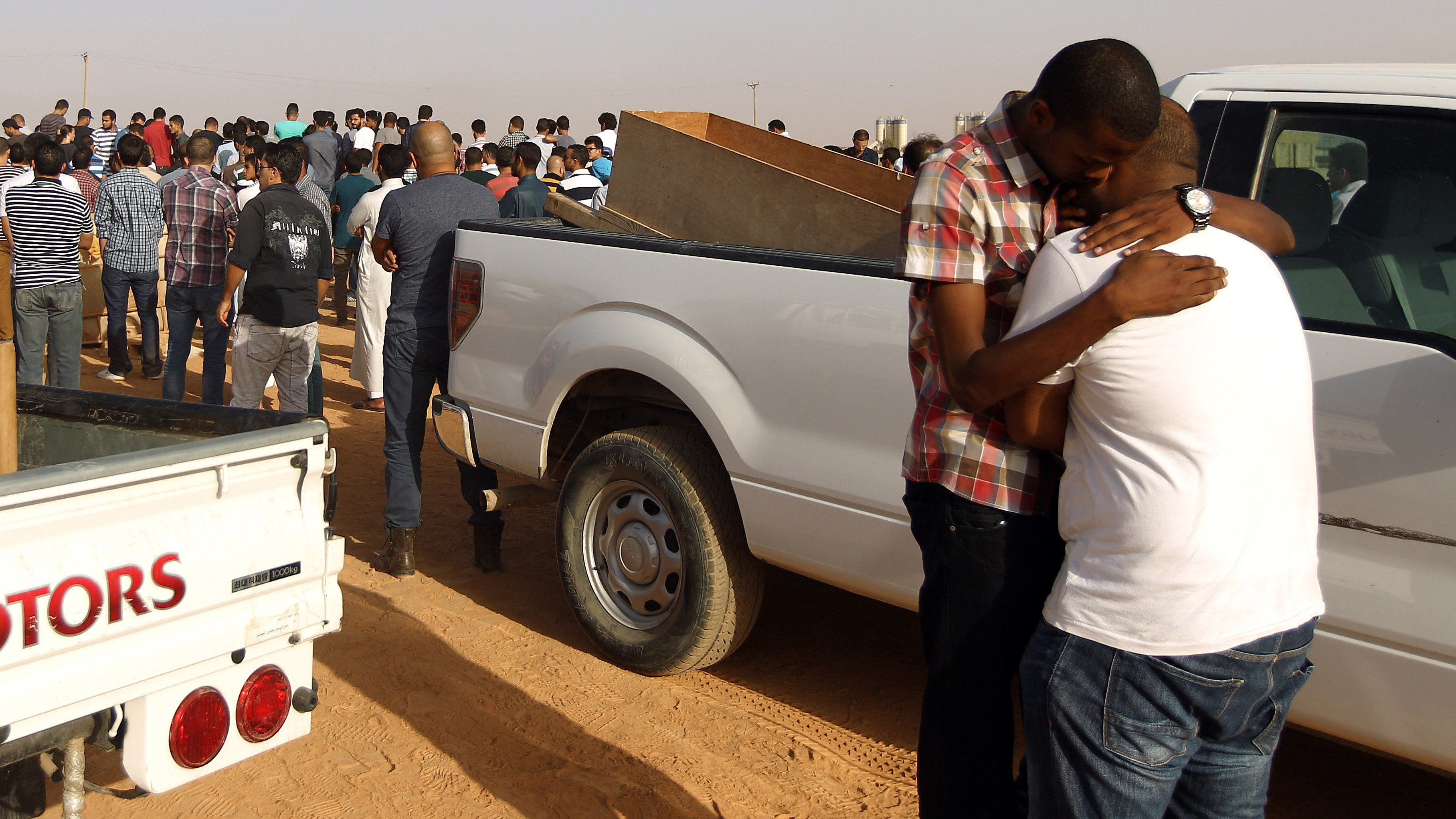 Two men hug during the funeral for Libyan activist Tawfik Bin Saud in Benghazi on September 20, 2014. Tawfik was killed, along with a friend, late on September 19, by unknown gunmen as they were driving home in Libya's eastern coastal city of Benghazi.