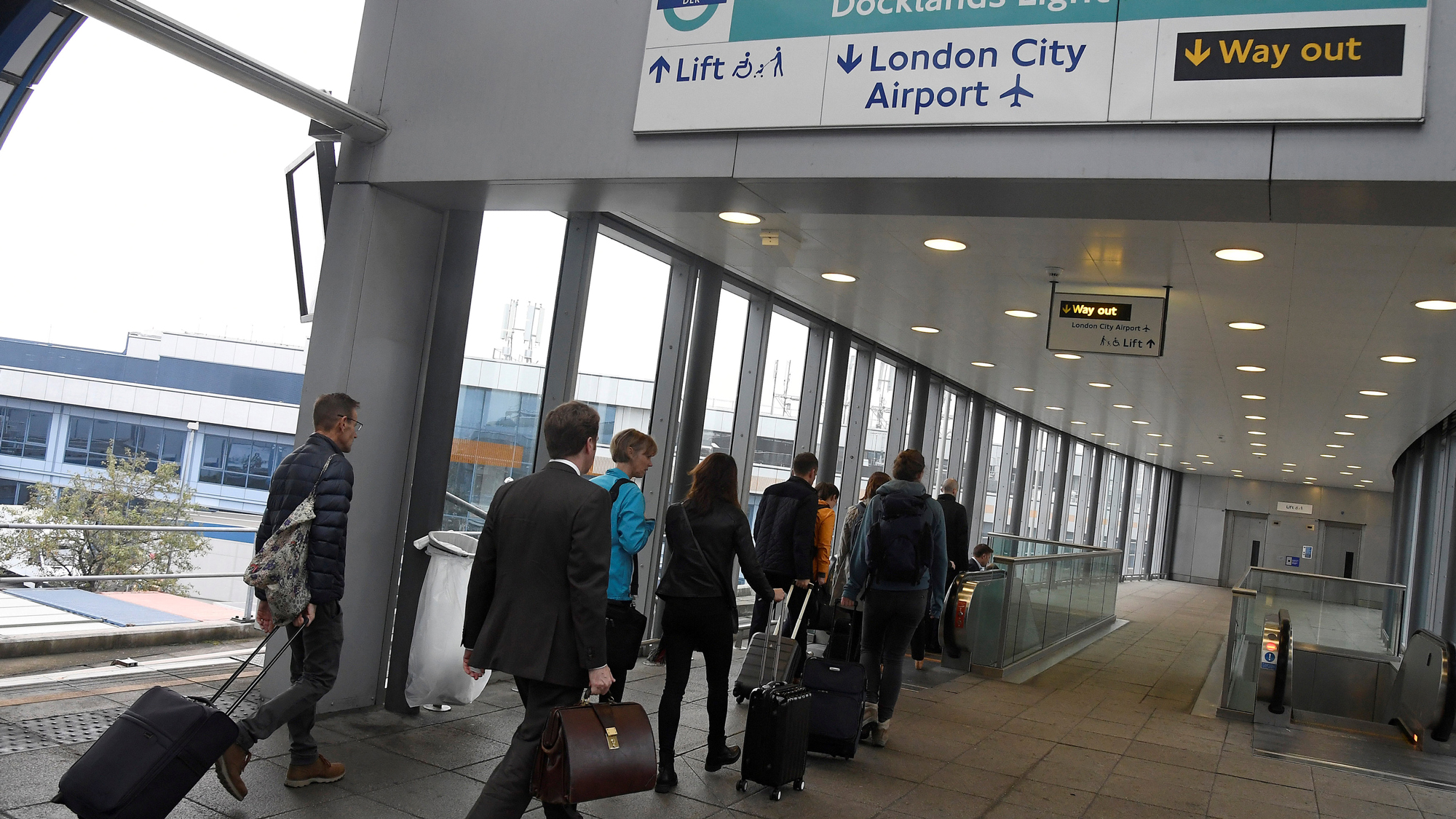 Passengers alight from a train to enter City Airport in London, Britain.