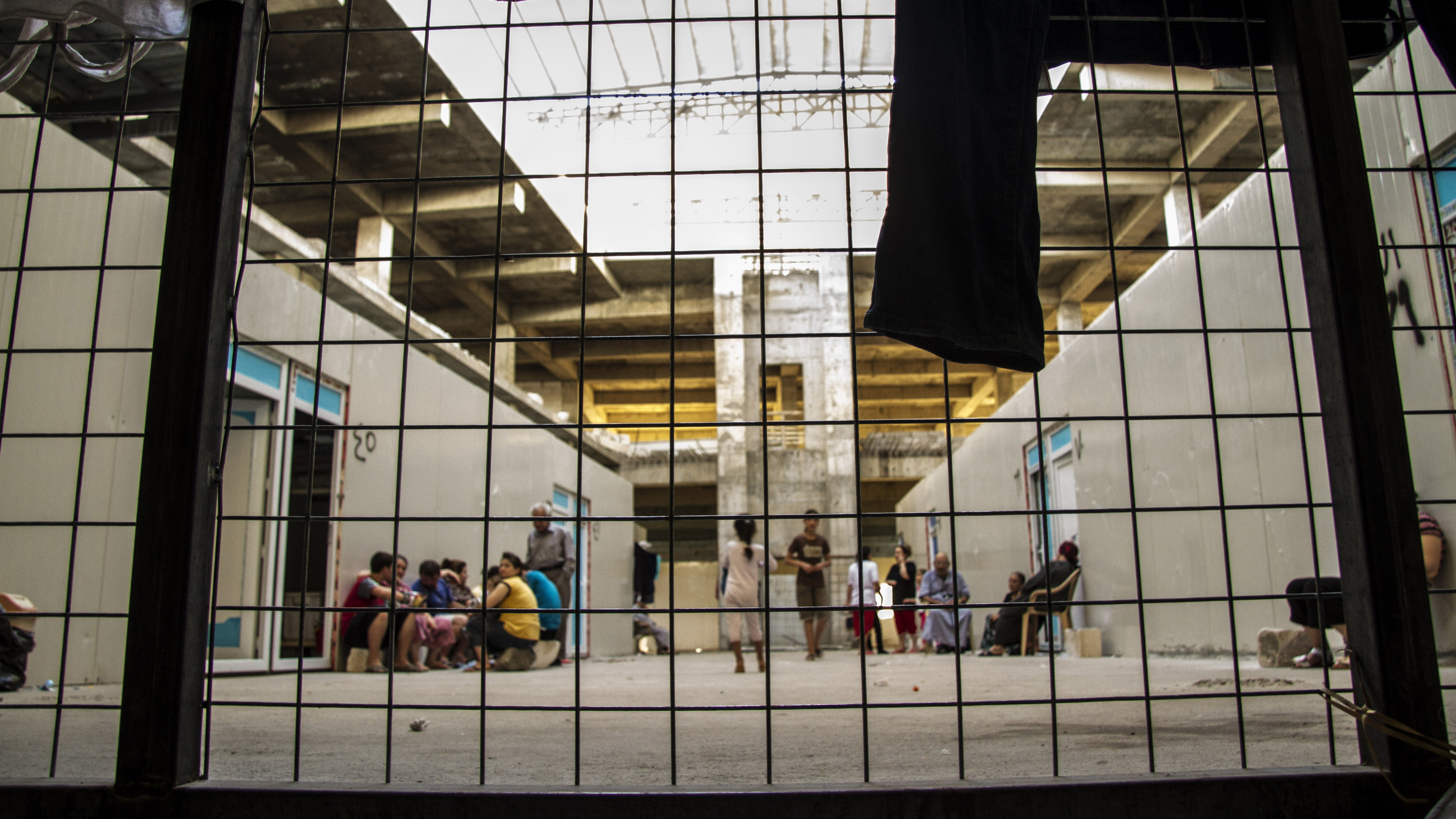 The main atrium of this would-be mall is now home to hundreds of Iraqis from villages outside Mosul. Here the concrete floors and walls give families more protection than the displaced families living in tents in a public park just across the street.