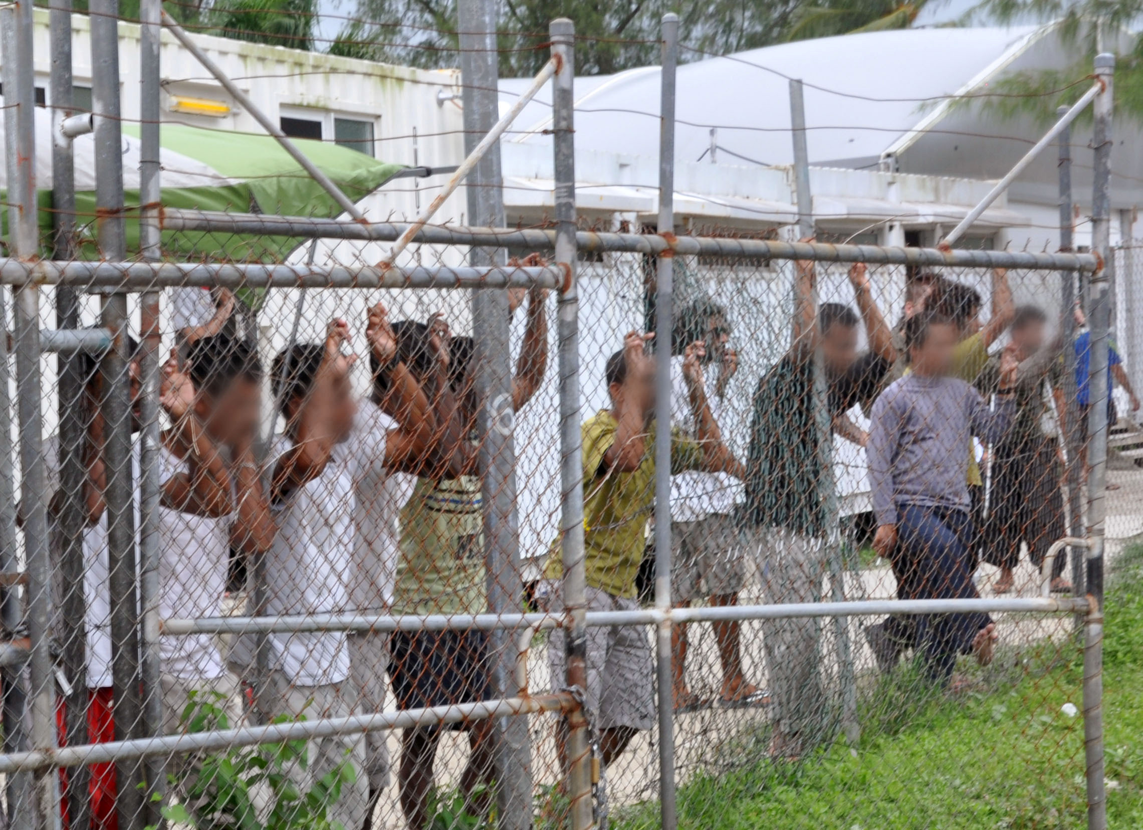 Asylum-seekers look through a fence at the Manus Island detention center in Papua New Guinea March 21, 2014. It is scheduled to close October 31, 2017. Eoin Blackwell/AAP/via Reuters/File Photo ATTENTION EDITORS - FACES PIXELLATED AT SOURCE. THIS PICTURE