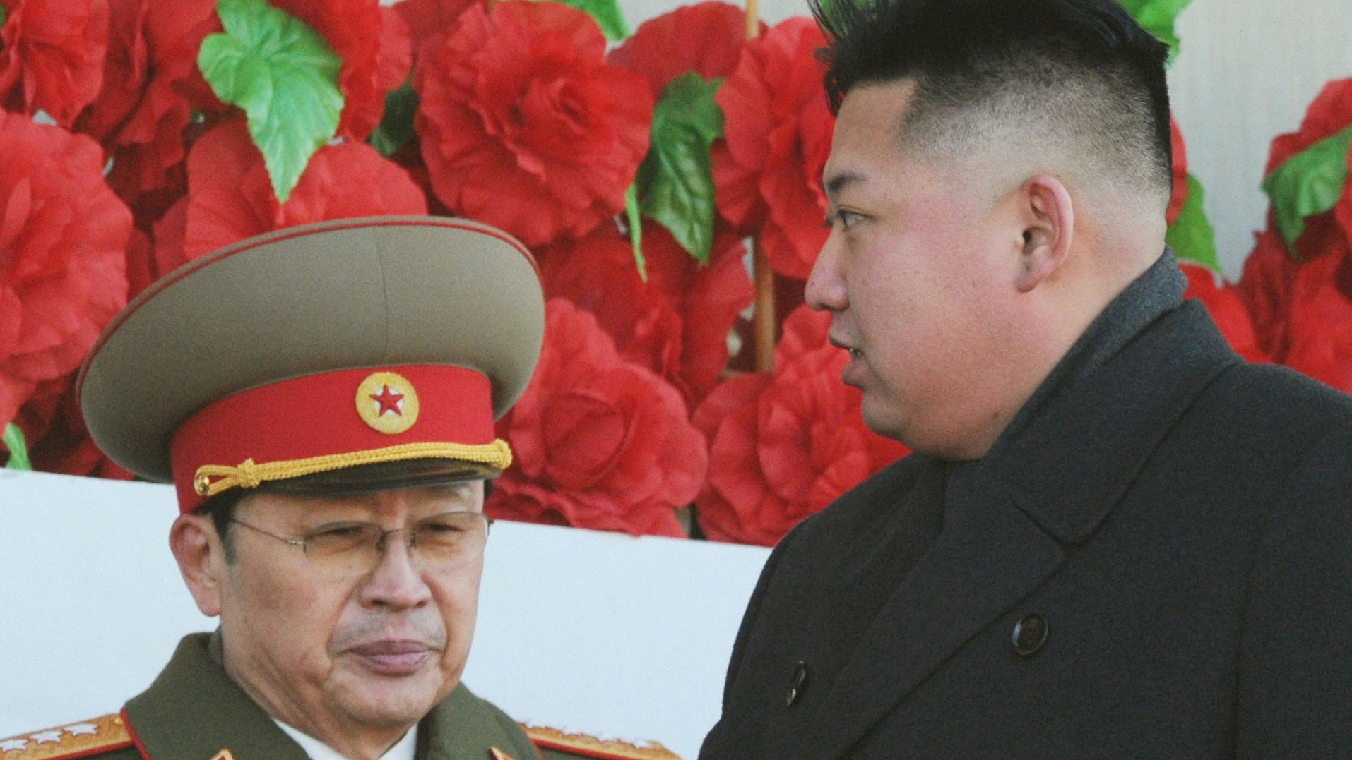 Jang Song-thaek in army uniform standing with his nephew and North Korea's top leader, Kim Jong-un, at a military parade in Pyongyang (February of 2012).