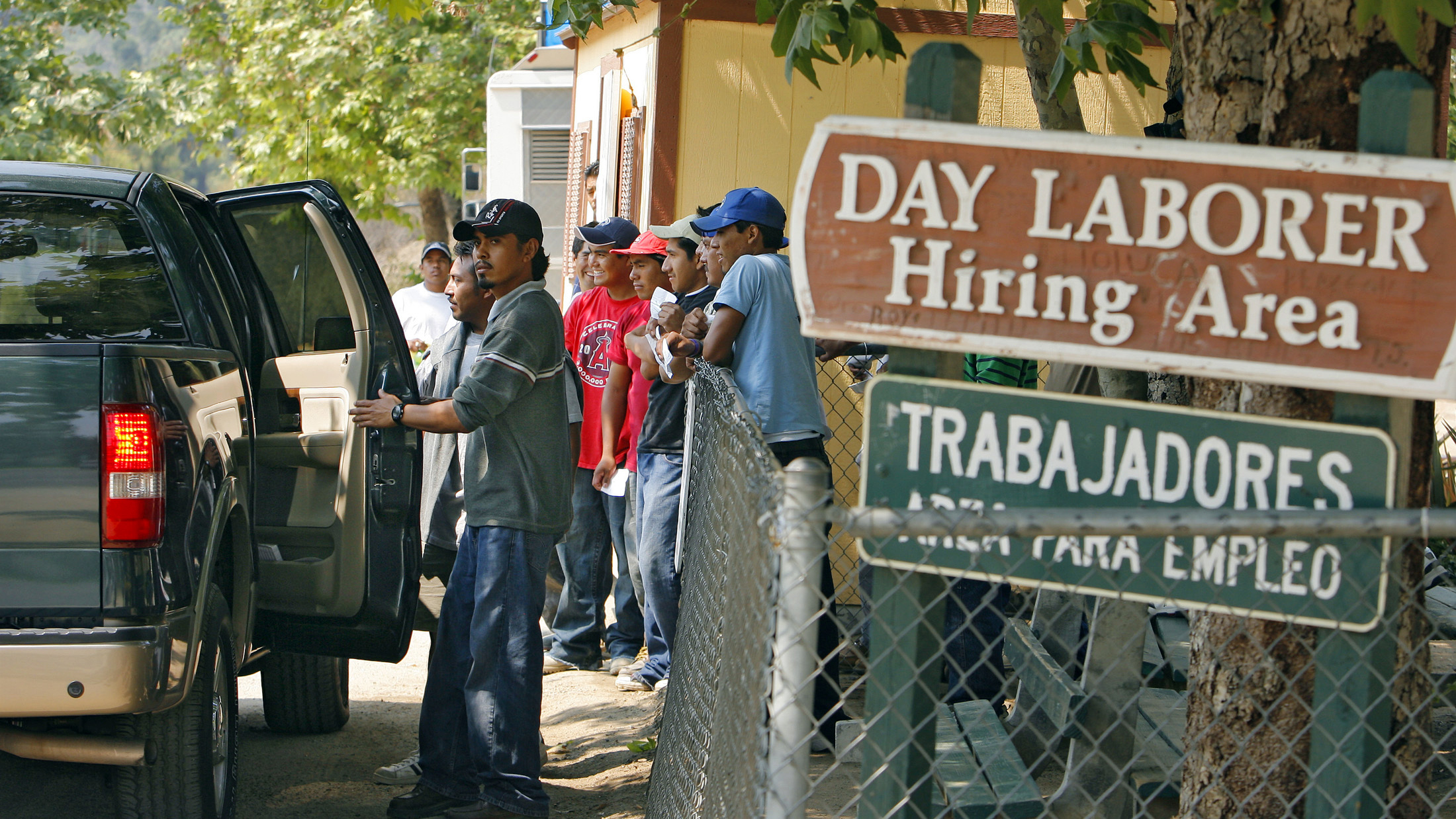 Day laborers enter a truck after being chosen by an employer at a hiring area in Laguna Beach, California