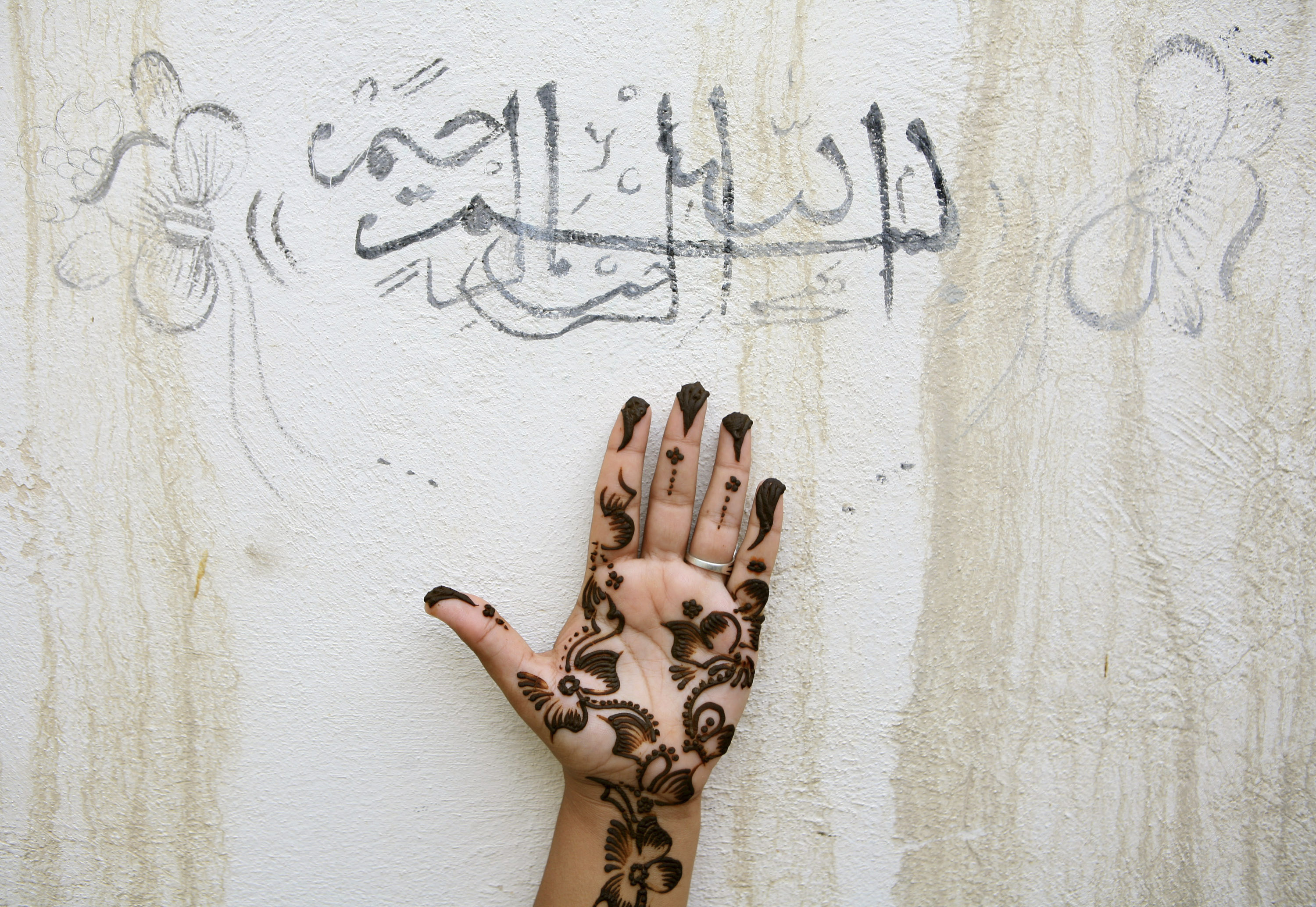 """An Iranian woman holds up her hand, painted with henna, under a religious sentence as she prepares for a wedding ceremony in the city of Qeshm on Qeshm Island at the Persian Gulf, November 1, 2006. The sentence reads, """"In the name of Allah, the Beneficent"""
