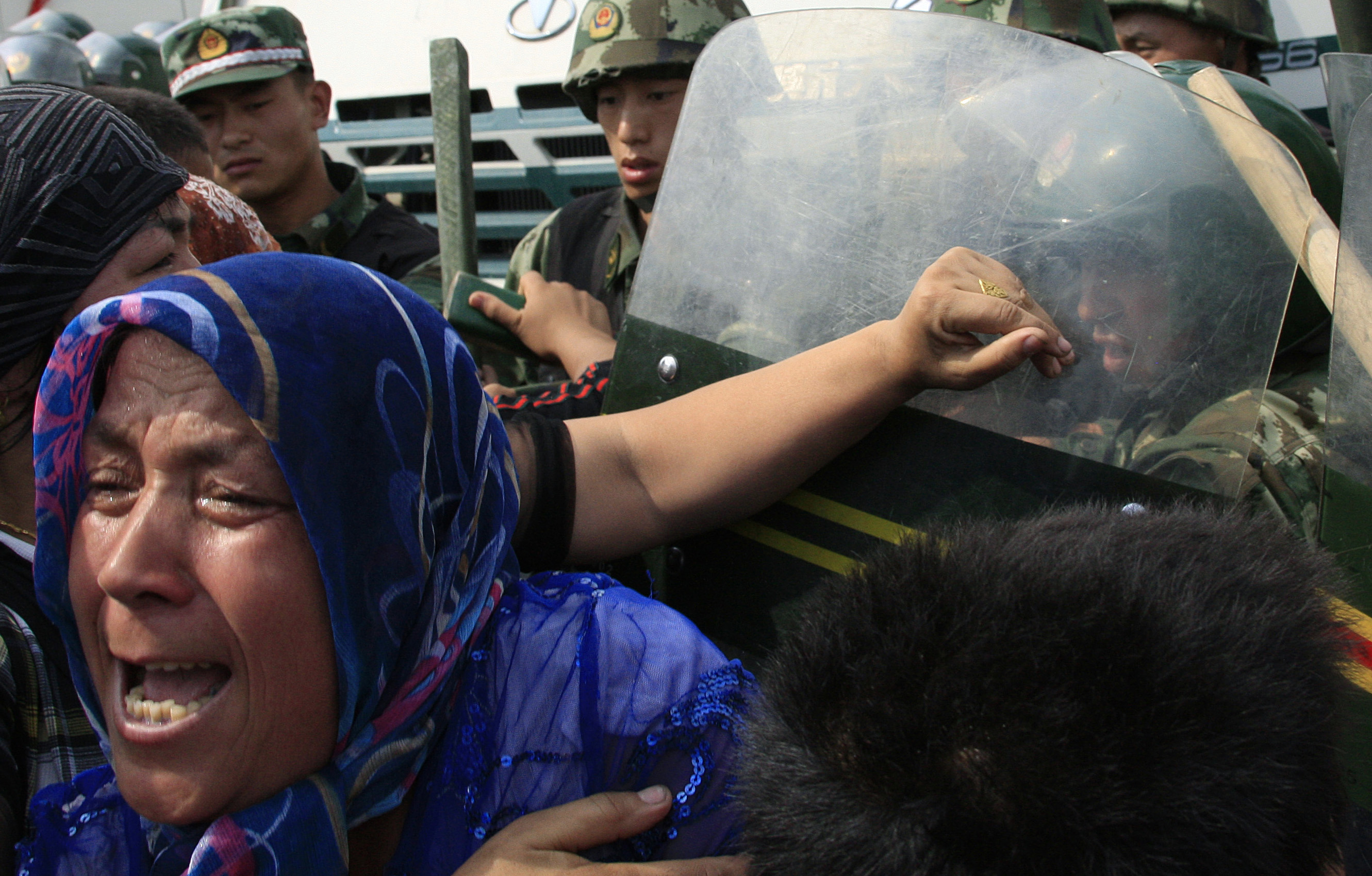 A woman pushes at Chinese paramilitary police wearing riot gear as a crowd of angry locals confront security forces on a street in the city of Urumqi in China's Xinjiang Autonomous Region on July 7, 2009.