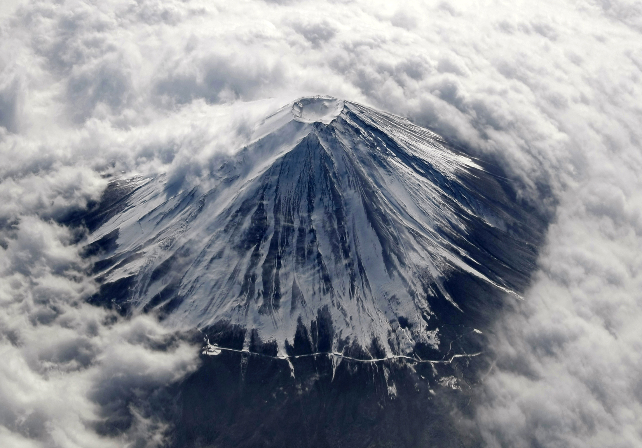 Japan's Mount Fuji, covered with snow and surrounded by cloud, is seen from an airplane February 2, 2010. Mount Fuji, at 3,776 metres (12,388 ft) is Japan's highest mountain.