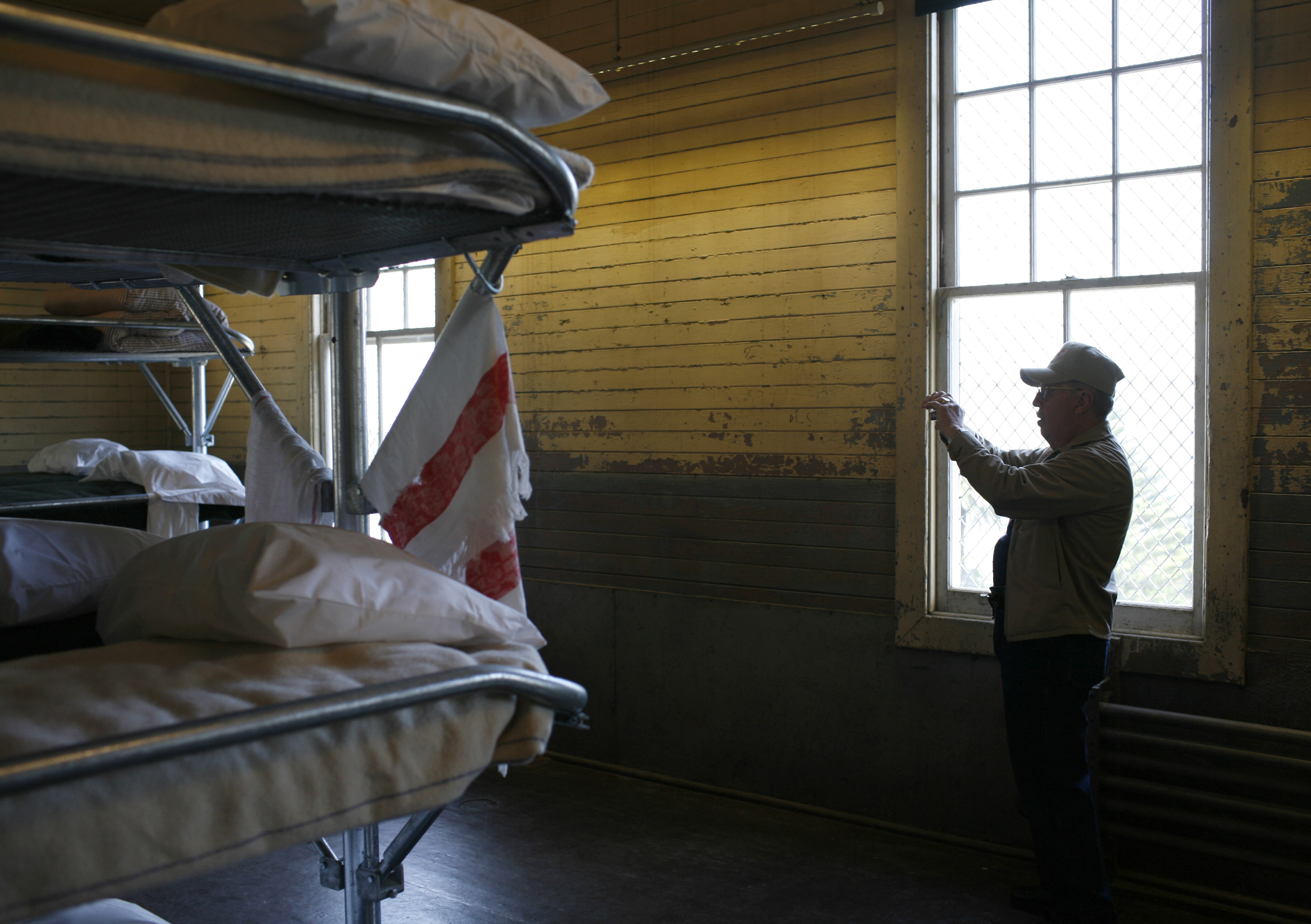Bunk beds in cell, with man taking photo will cell phone