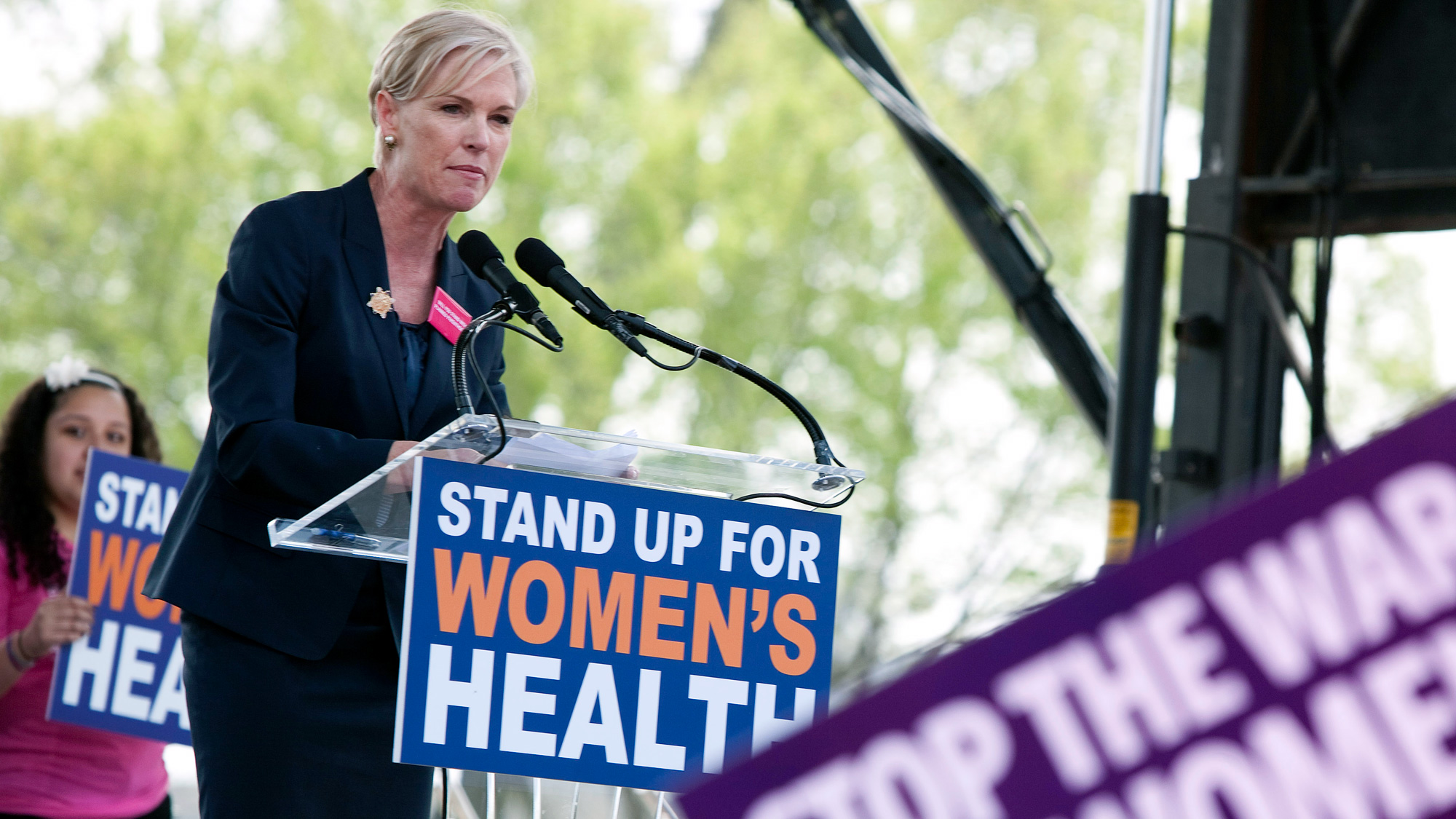 """A blond woman is speaking into a microphone at a podium with a sign on the front that says """"Stand up for women"""""""