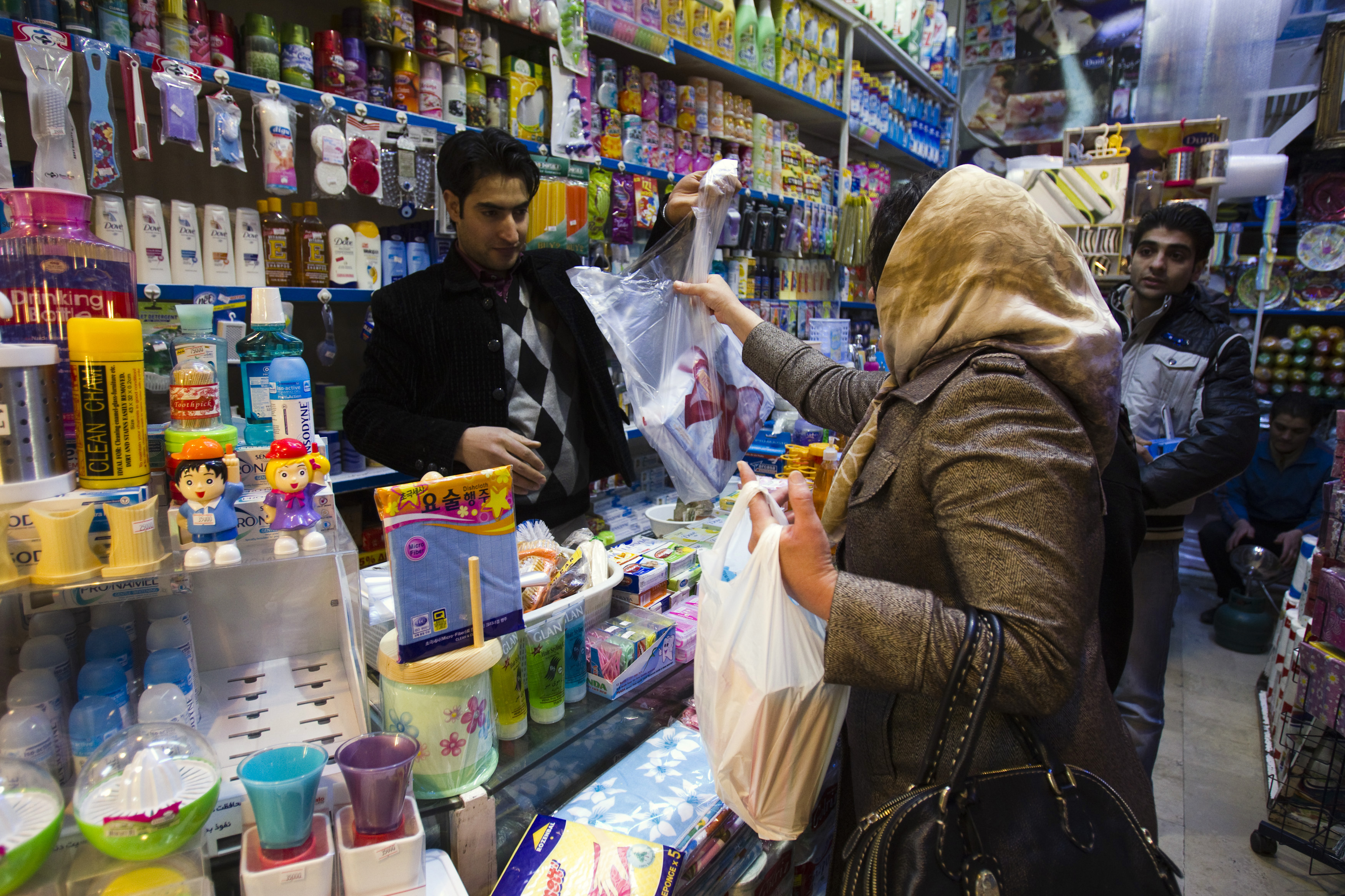 A woman makes a purchase at a store in Tehran.