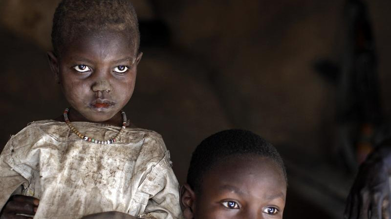 A girl and her brother shelter in a cave during an air raid in the Nuba mountains of Sudan in 2012.