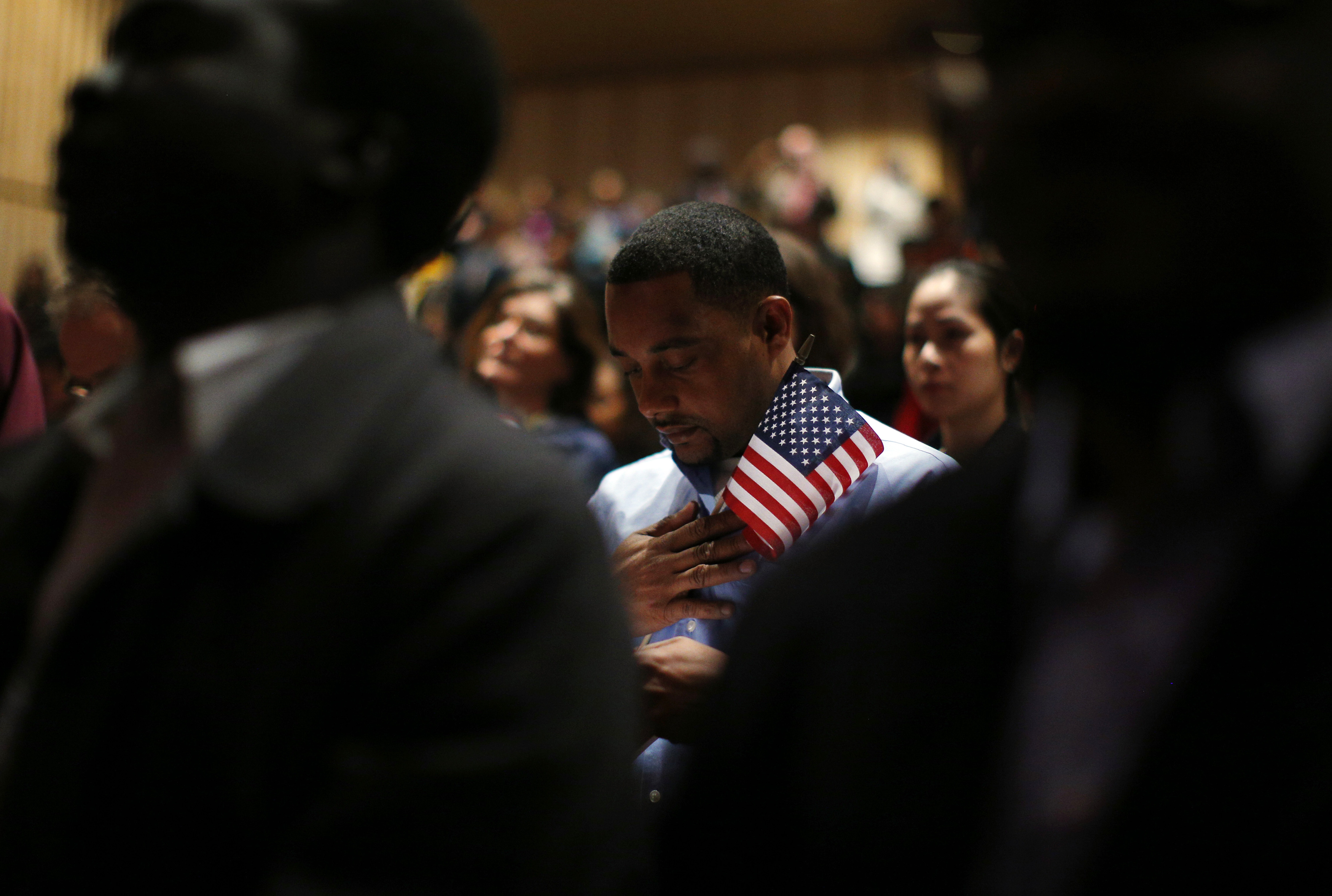 Immigrants stand for the invocation during a naturalization ceremony to become new U.S. citizens in Boston, 2013. Massachusetts is home to thousands of refugees, but the mayor of Springfield, Mass. says refugees are draining his city's resources.