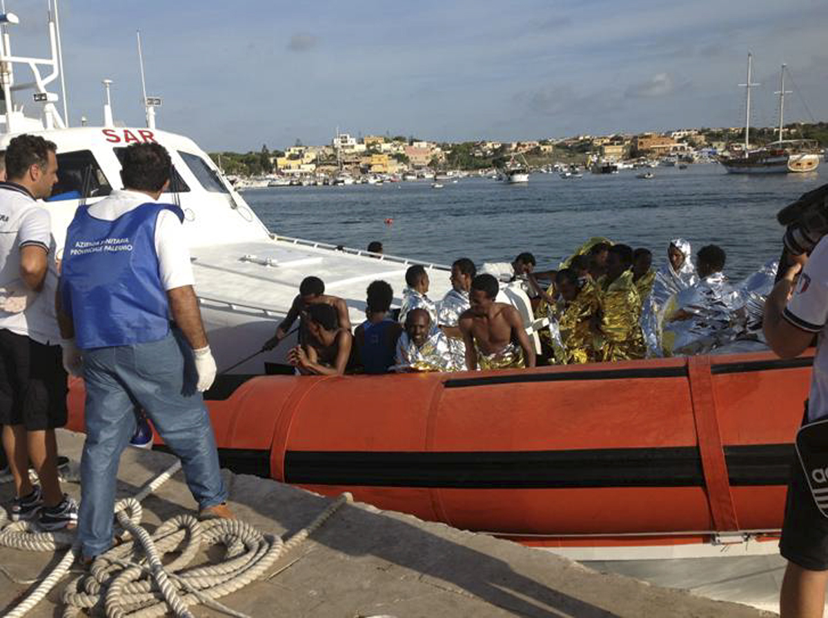 Rescued migrants on board a coastguard vessel arrive at the harbor of Lampedusa.