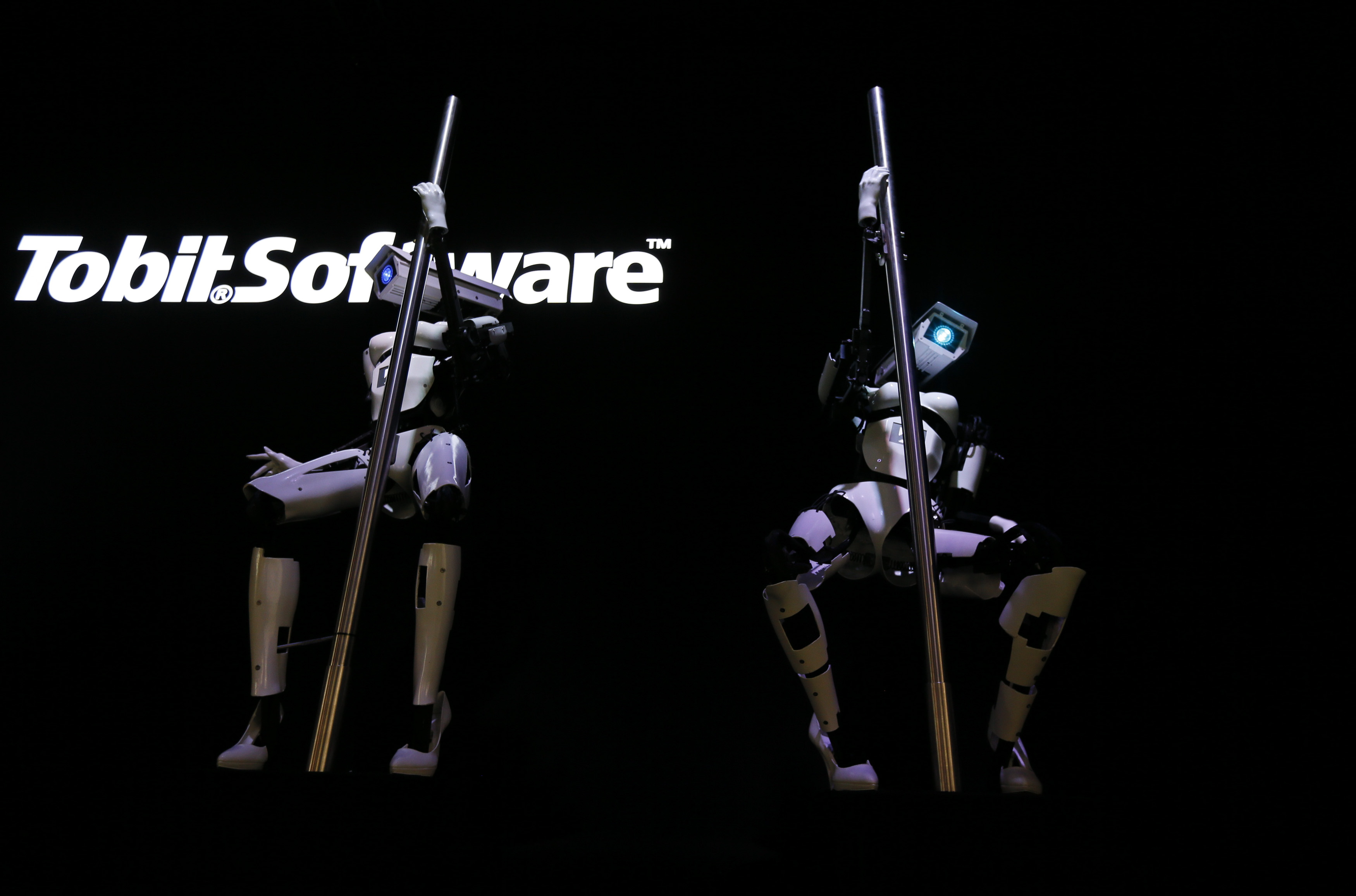"""""""Female"""" robots Tessy and Tess wear white stiletto heels and pole dance during a demonstration at the Tobit Software stand at the 2014 CeBIT trade fair in Hanover, Germany."""
