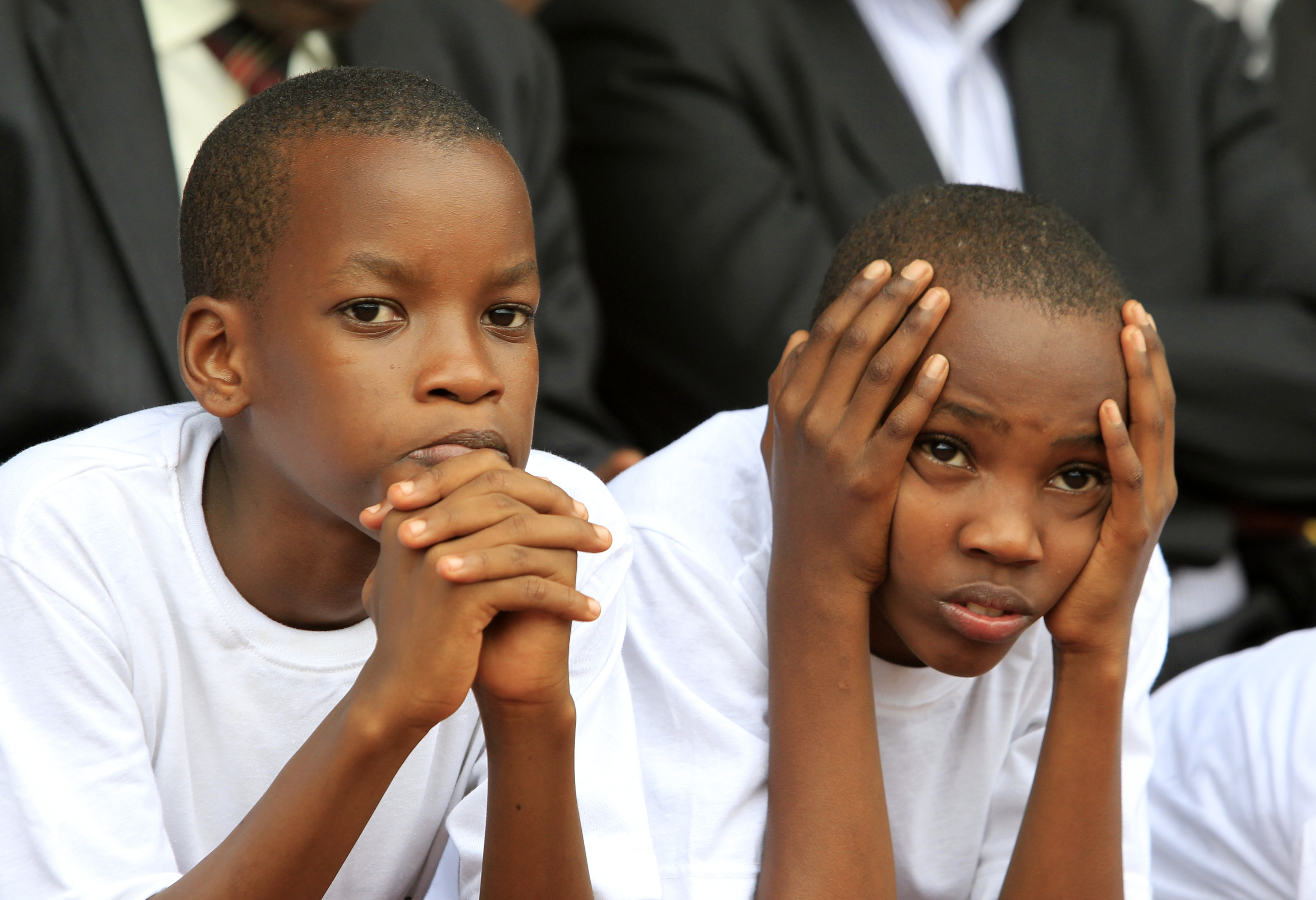 Rwandan boys watch as a flame is escorted through a Kigali suburb marking the 20th anniversary of the genocide.