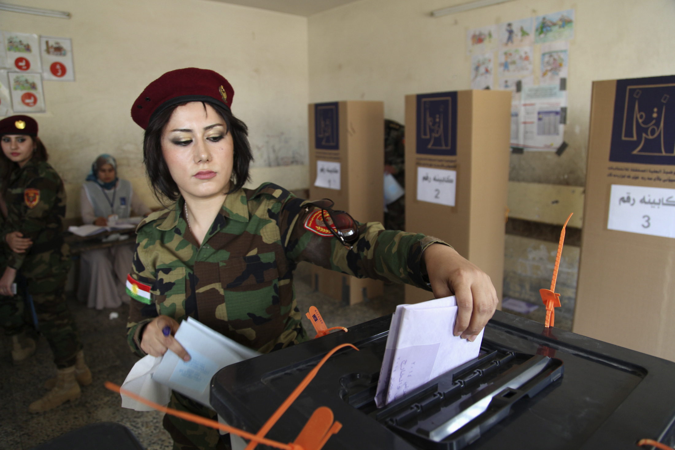 A member of Kurdish security forces casts her ballot inside a polling station during early voting for the parliamentary election in Irbil, in Iraq's Kurdistan region, on April 28, 2014.