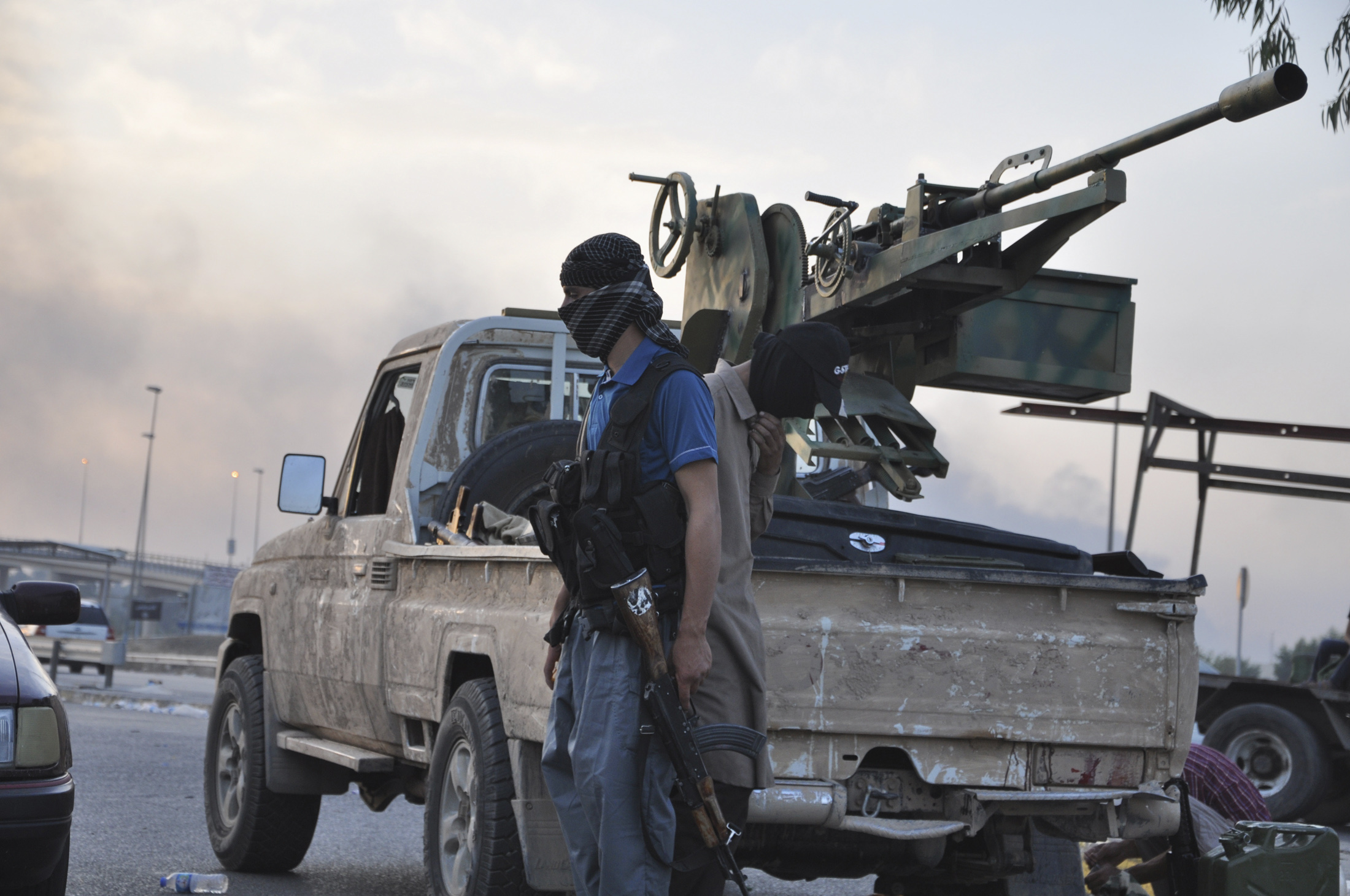 ISIS fighters stand guard at a checkpoint in the northern Iraq city of Mosul, June 11, 2014.