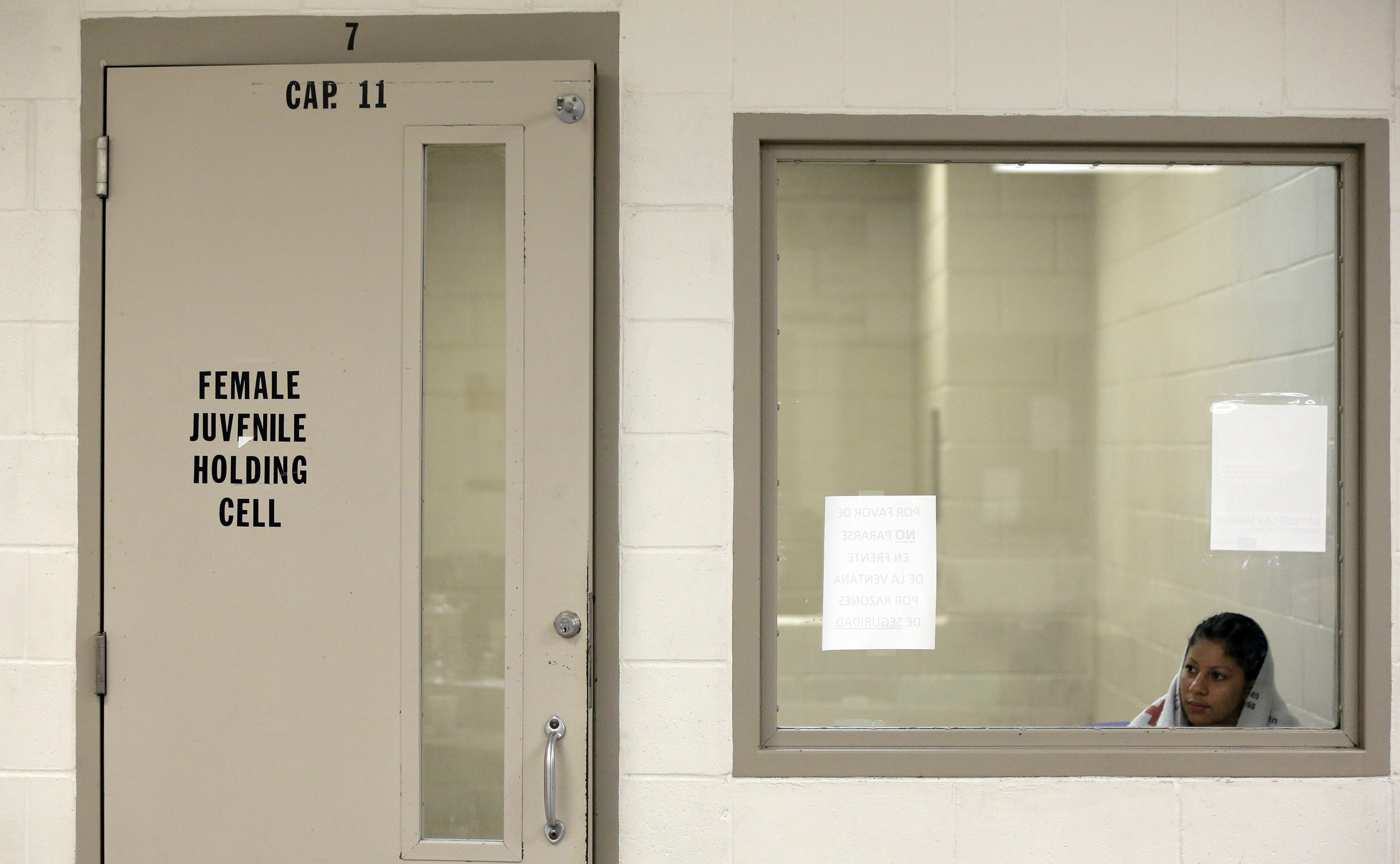 A woman looks out a window of a holding cell