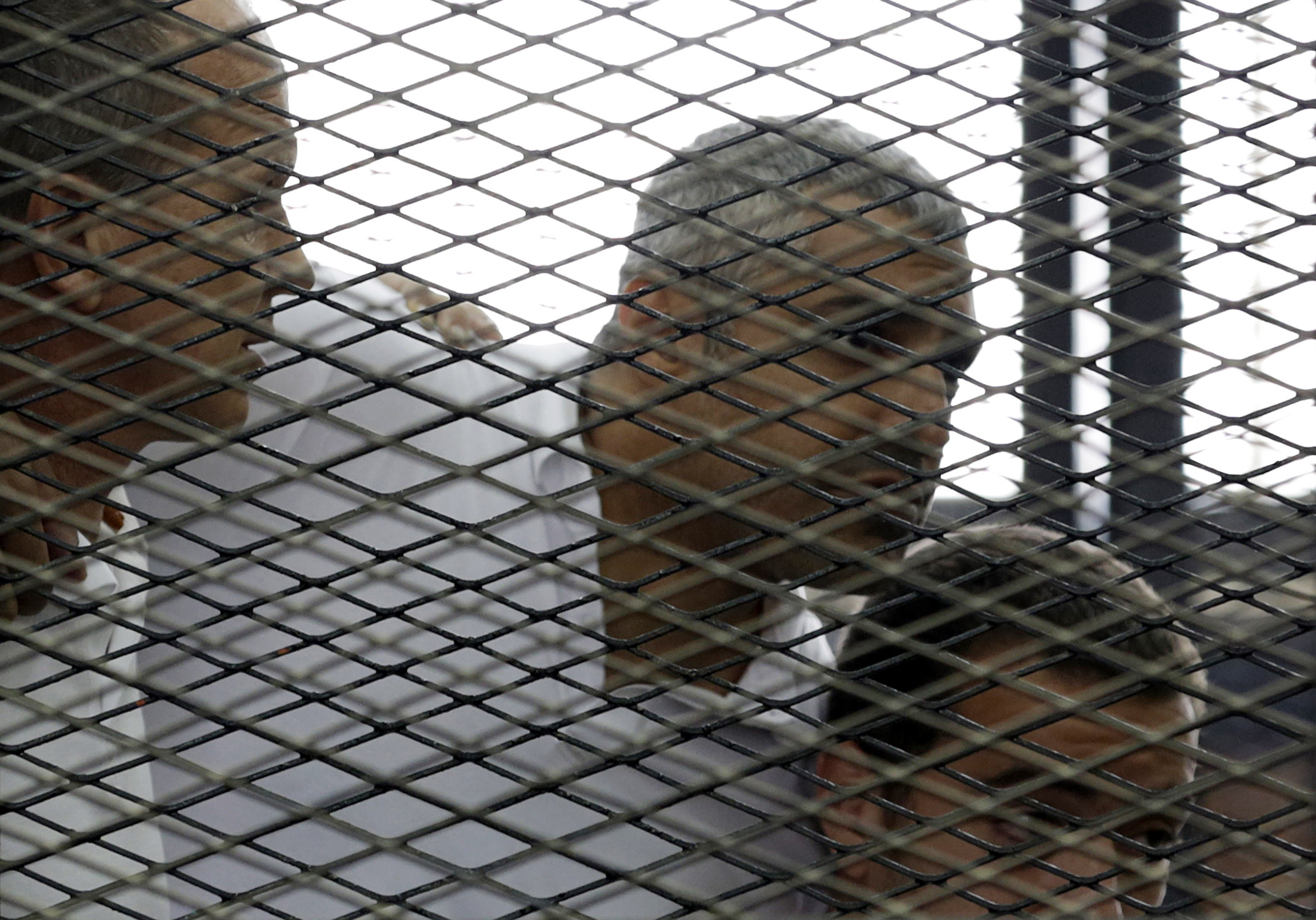 """Peter Greste, Mohamed Fahmy and Baher Mohamed (L to R) listen to a ruling at a court in Cairo June 23, 2014. The three Al Jazeera journalists were jailed for seven years in Egypt on Monday after the court convicted them of helping a """"terrorist organizatio"""