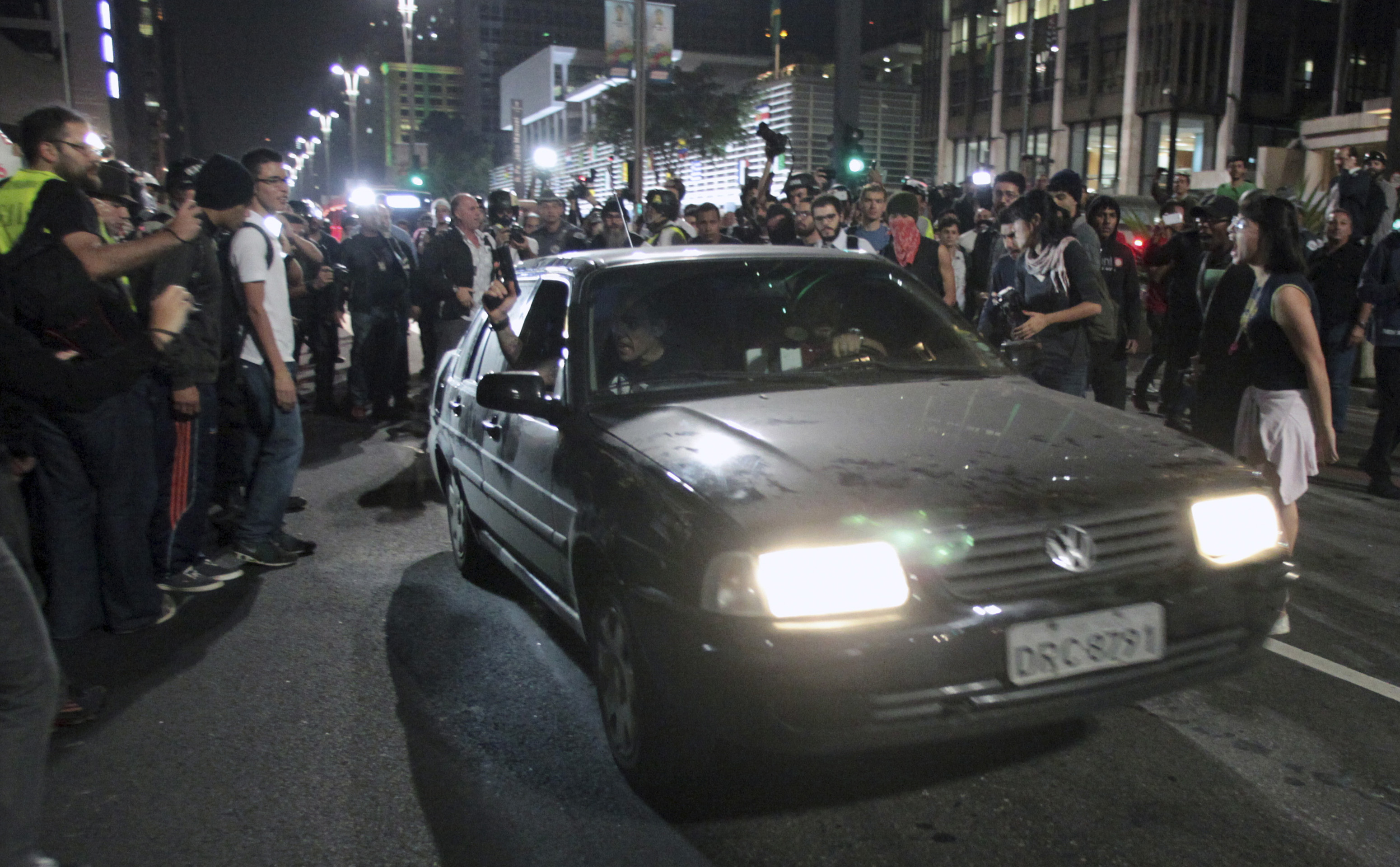 A Brazilian policeman pulls a gun out of the window of a car during a June 23 protest against the World Cup on a street in São Paulo. Activists say the arrests of two men at those protests were trumped up by police.