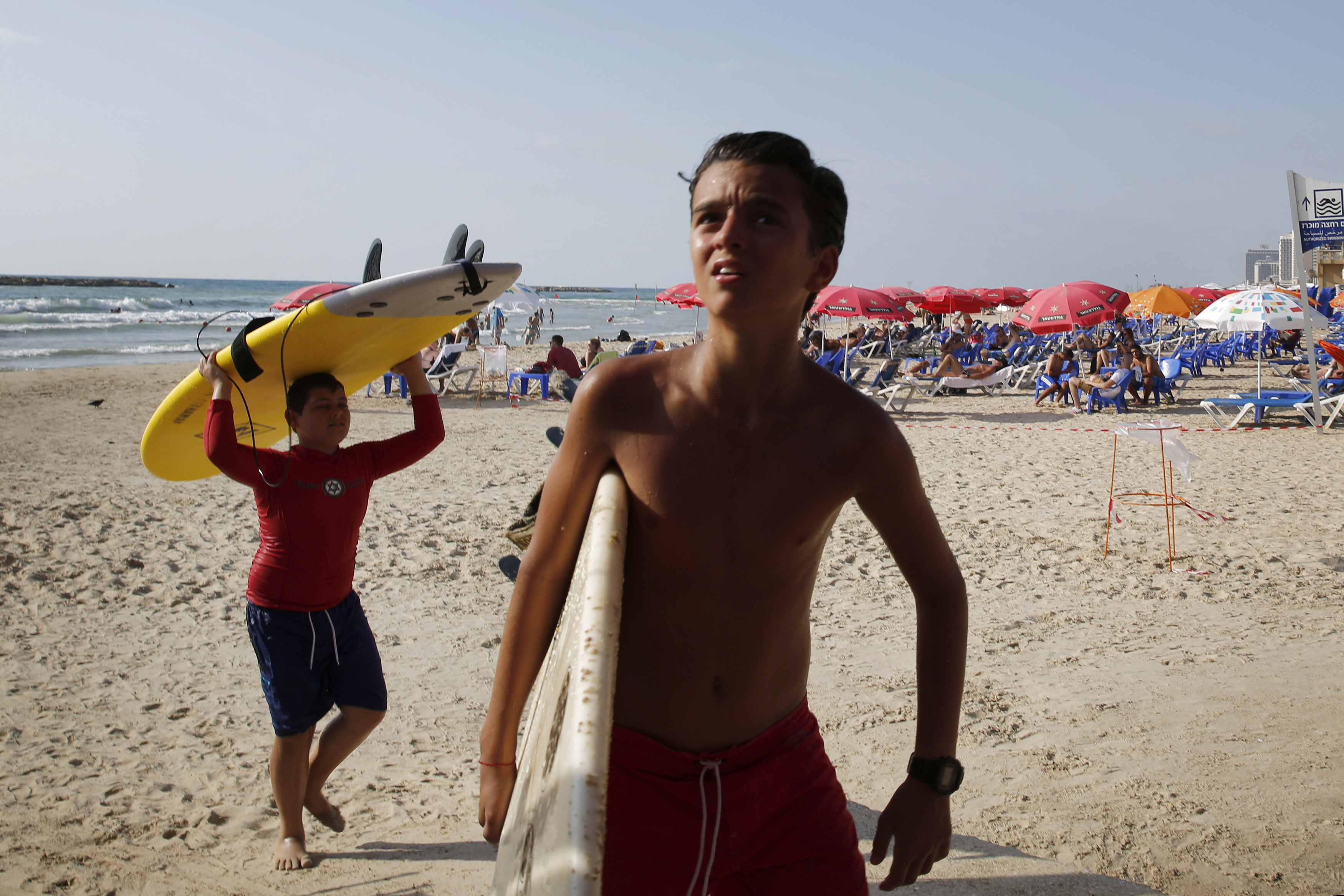 Boys carry their surfboards ashore on a Tel Aviv beach after their lesson was cancelled following a rocket from Gaza that was intercepted by Israel's Iron Dome defense system.