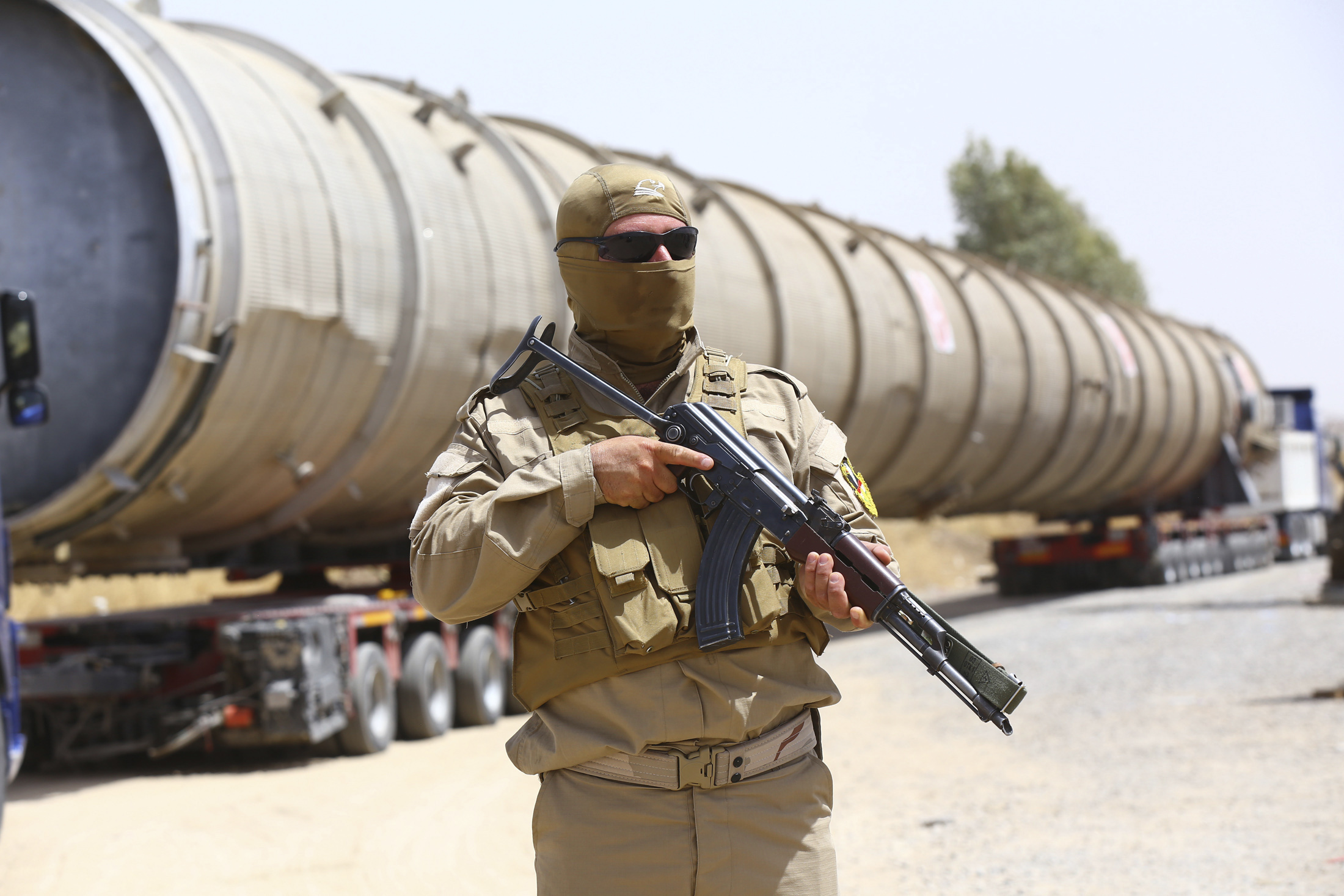 A member of the Kurdish security forces takes up position with his weapon as he guards a section of an oil refinery.
