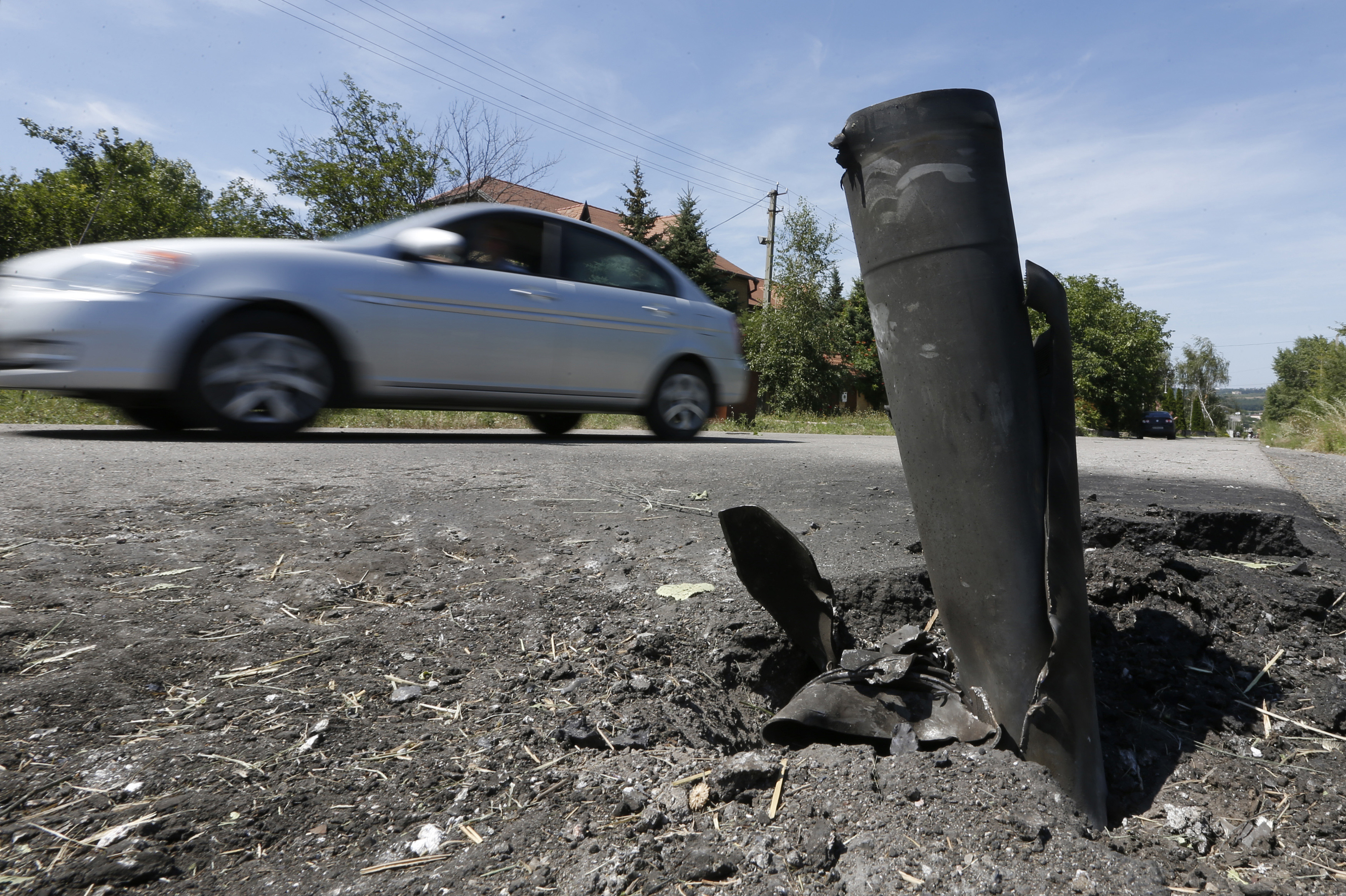 A car drives past the remains of a spent ammunition on the suburbs of Donetsk, Tuesday. Intense fighting between Ukrainian troops and pro-Russian rebels in eastern Ukraine killed dozens of civilians, soldiers and rebels, as Kiev pressed on with an offensi