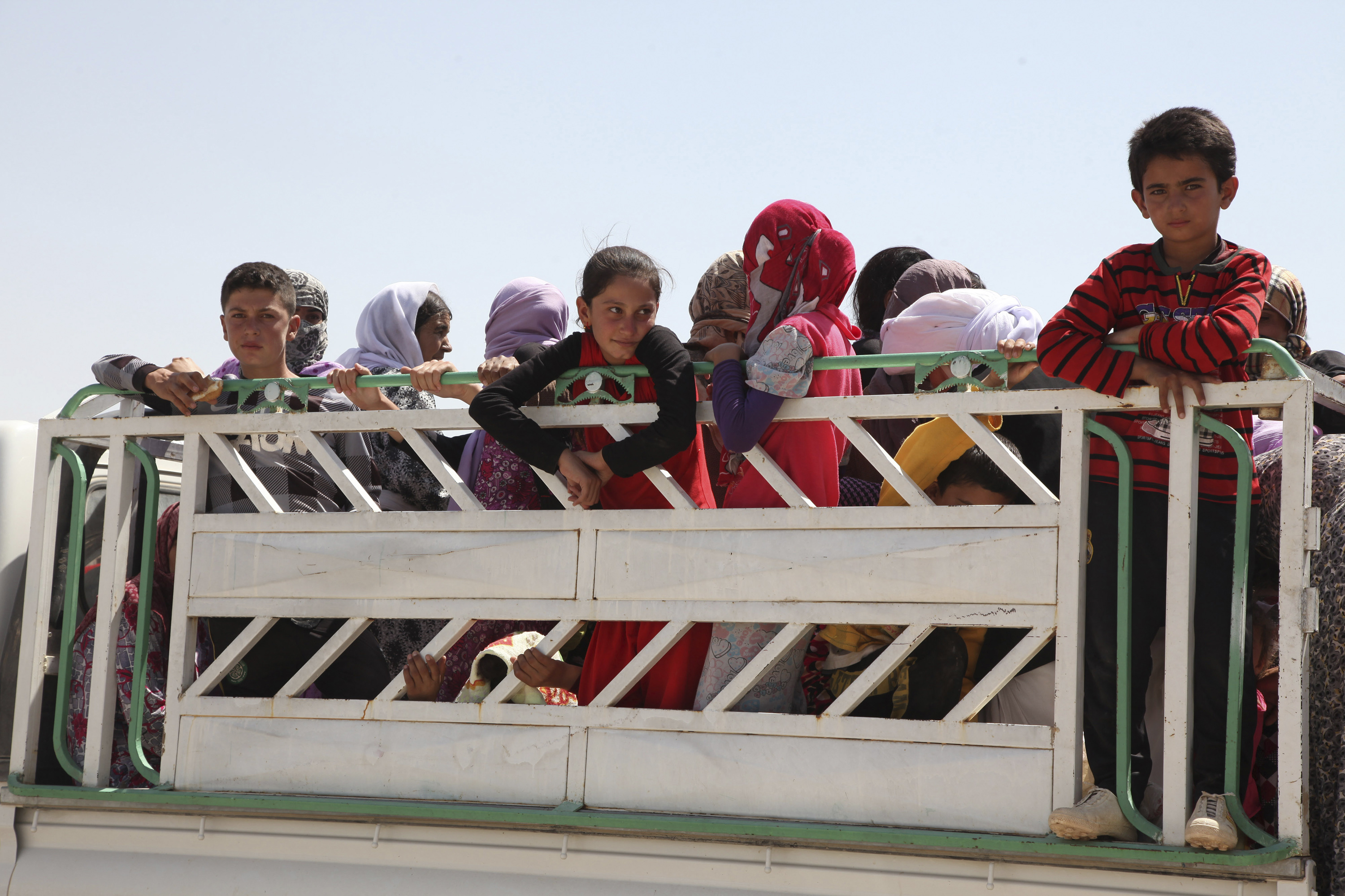 Displaced families from the minority Yazidi sect flee violence in the northern Iraqi town of Sinjar. Iraq's Prime Minister, Nuri al-Malik, ordered his air force for the first time to back Kurdish forces against Islamic State fighters after the Sunni milit