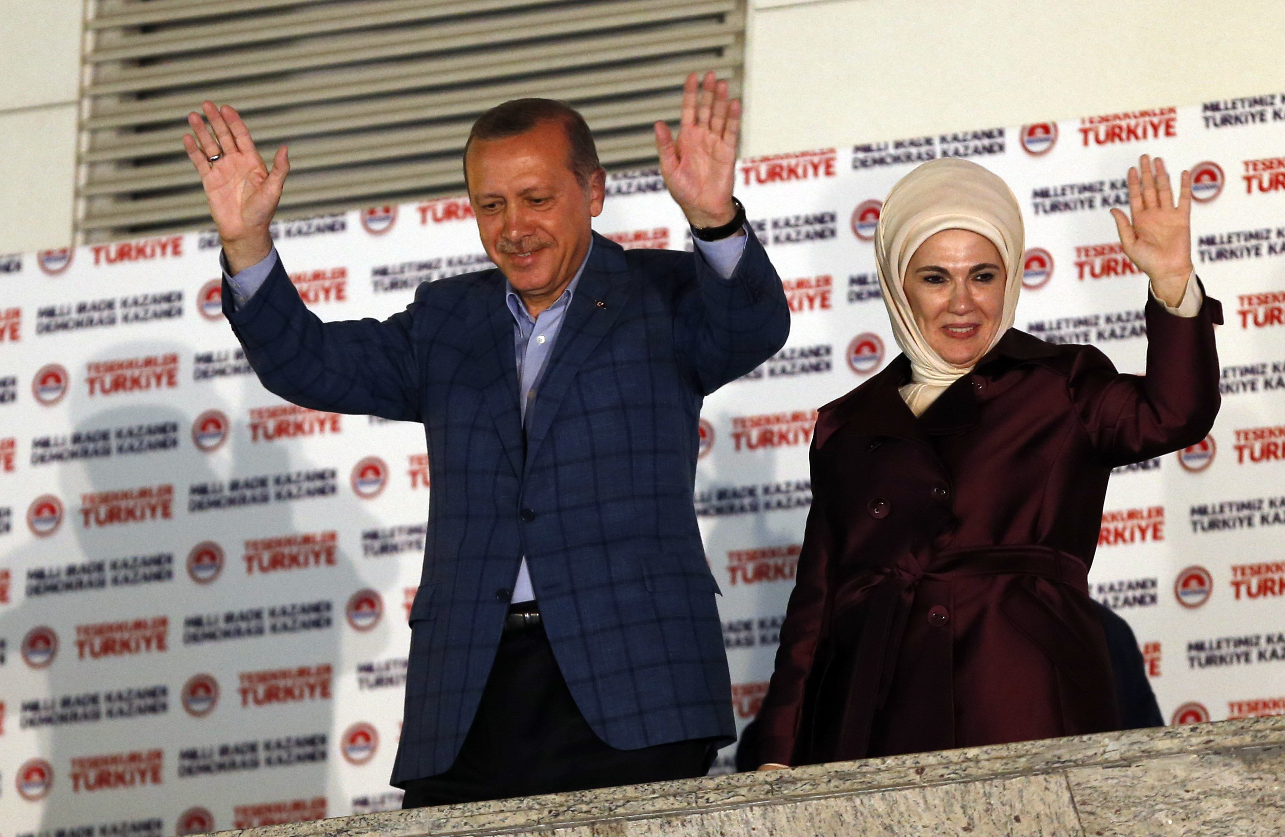 Recep Tayyip Erdogan, Turkey's Prime Minister, and his wife, Ermine, wave hands to supporters as they celebrate his election victory in front of the Justice and Development party headquarters in Ankara on August 10, 2014.