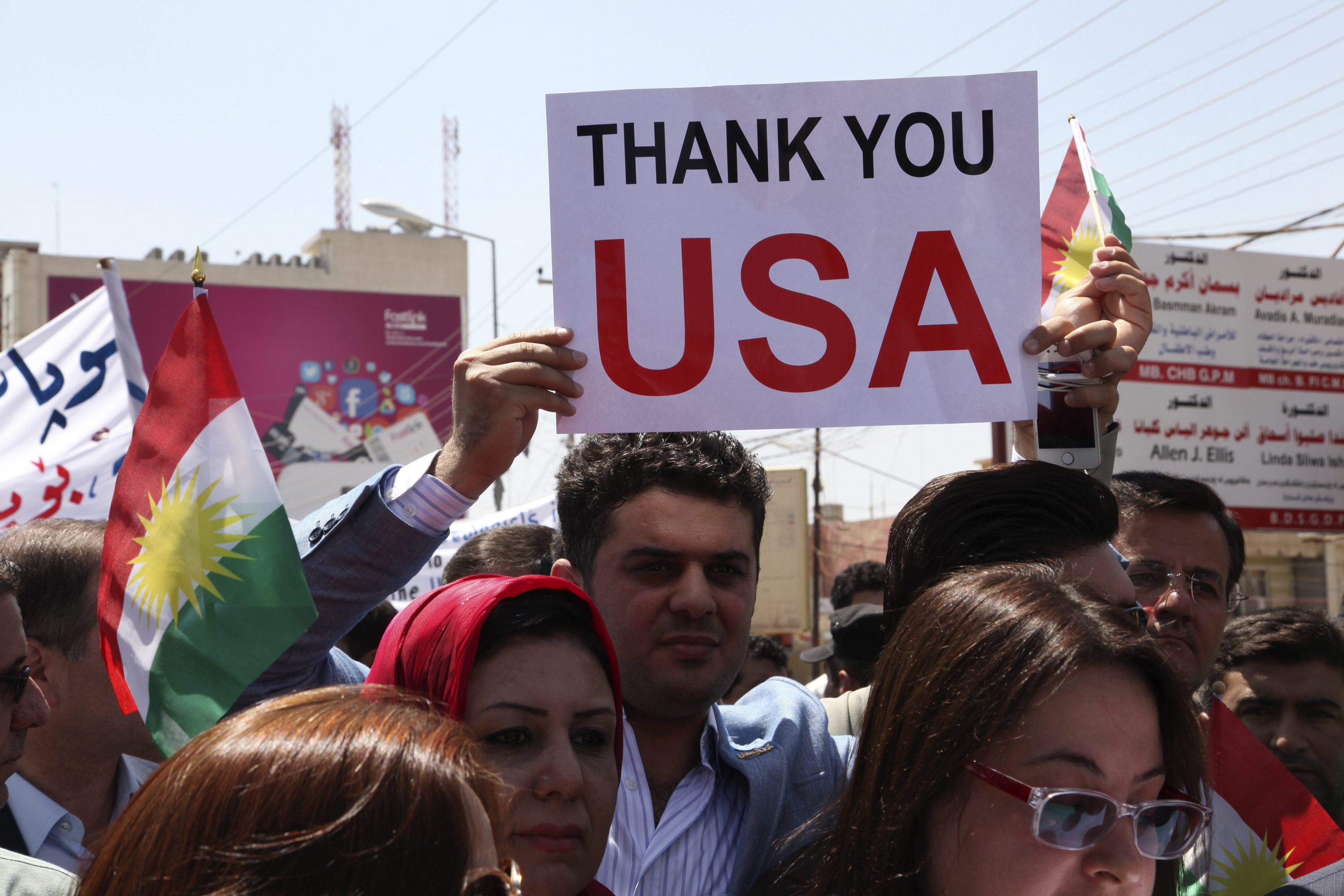A Kurdish resident holds a signs during a demonstration in support of peshmerga troops in front of the US consulate in Erbil, Iraq.