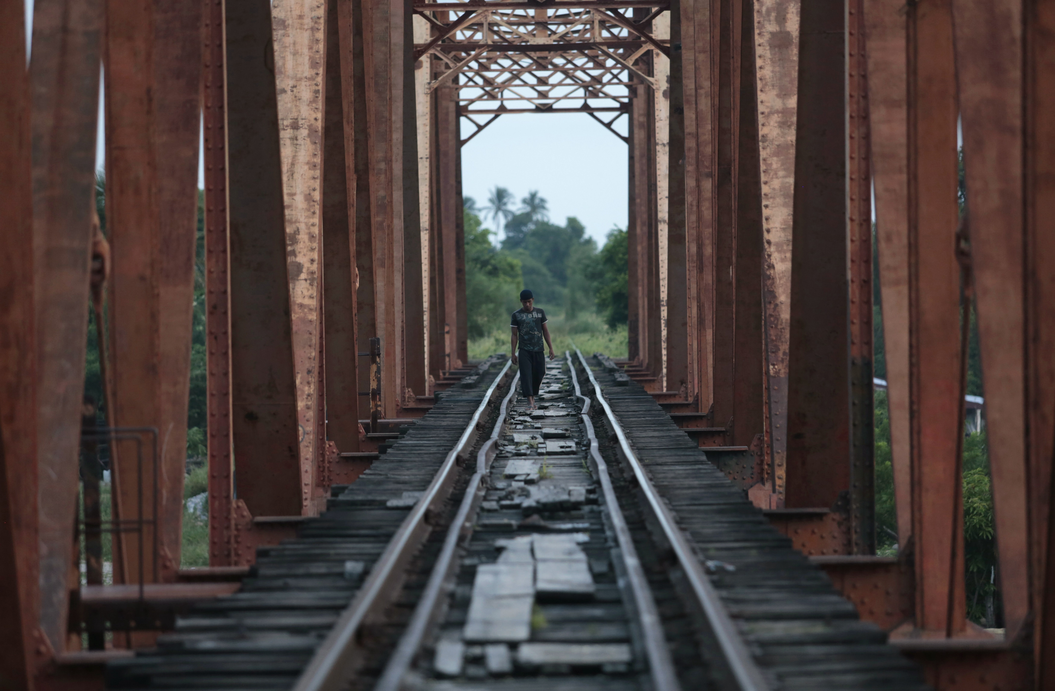 A Central American migrant walks on the train tracks in Mexico en route to the US border.