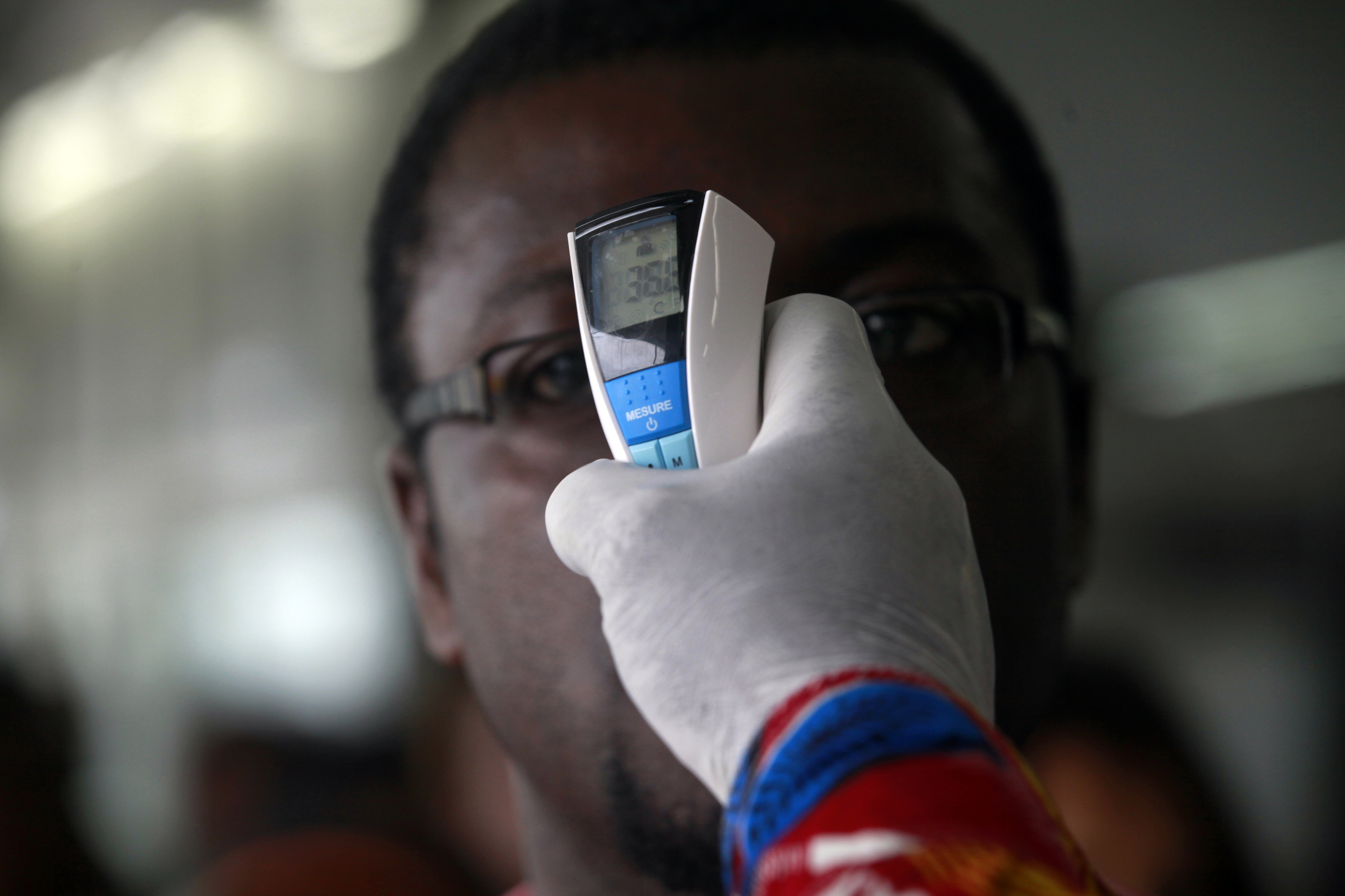 A health worker takes a passenger's temperature with an infrared digital laser thermometer at the Felix Houphouet Boigny international airport in Abidjan on August 13, 2014.
