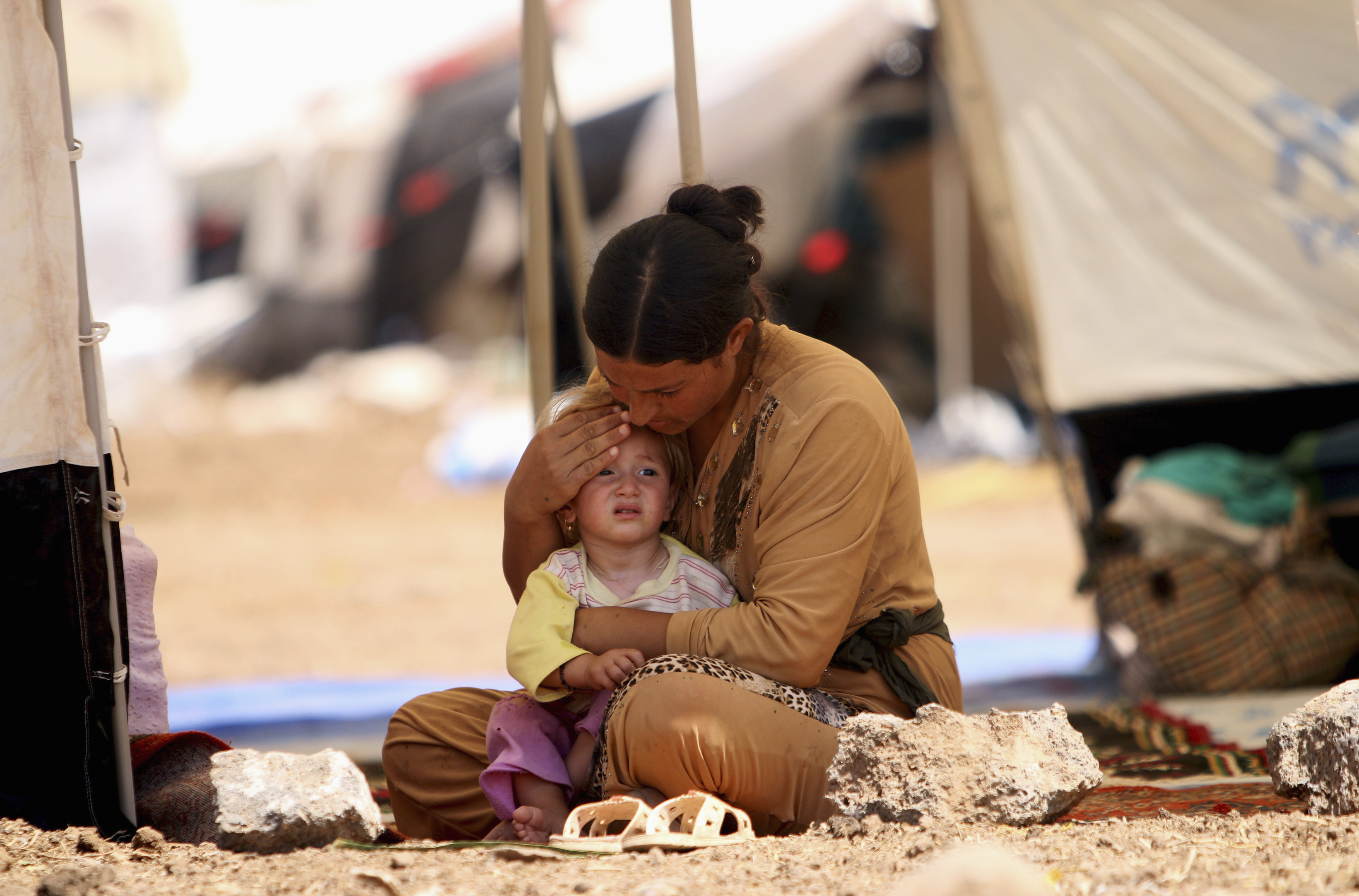 A refugee woman from the minority Yazidi sect, who fled the violence in the Iraqi town of Sinjar, sits with a child inside a tent at a refugee camp in north-eastern Syria. The Yazidis have been brutally persecuted by militants from the Islamic State, some