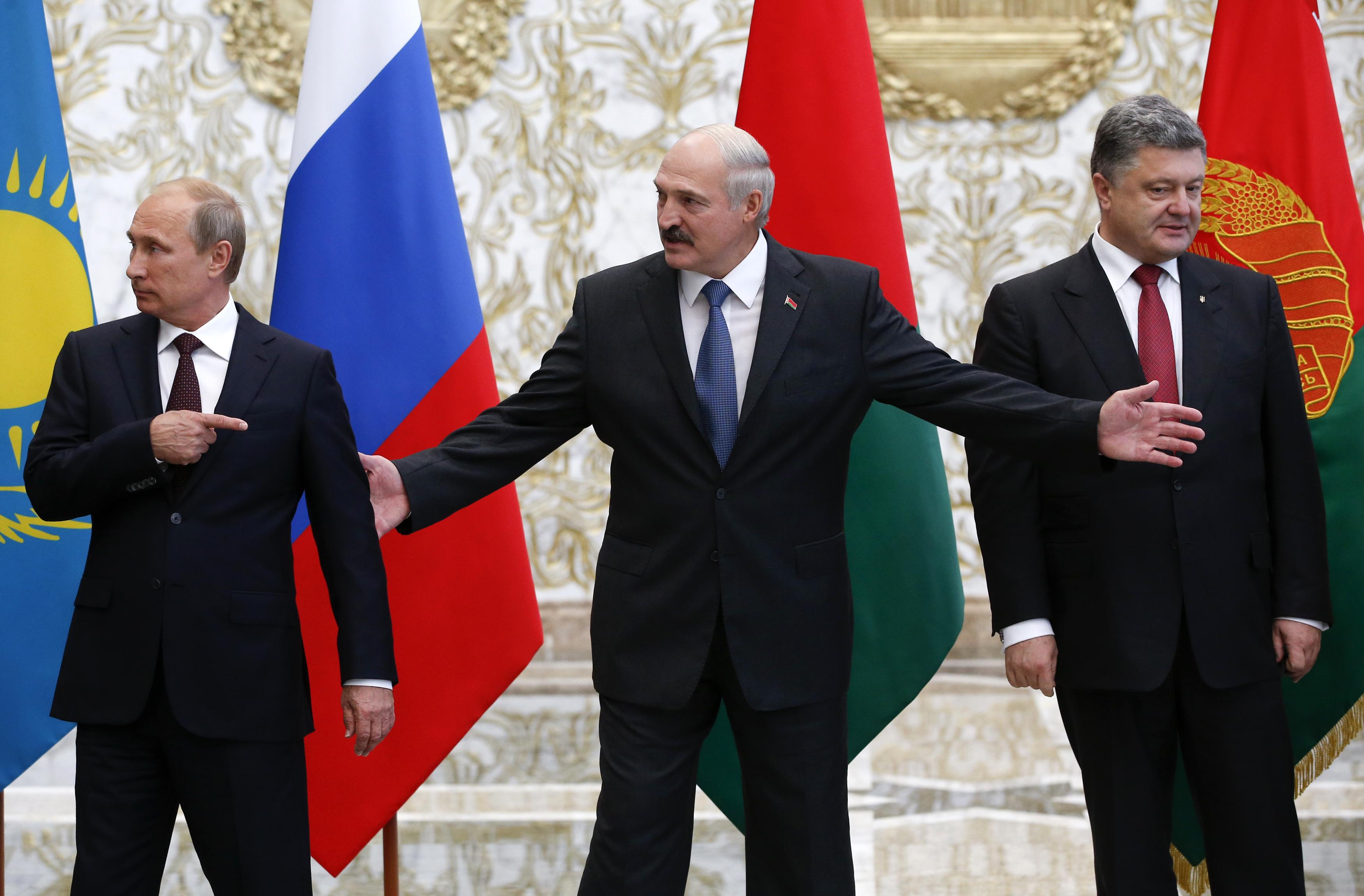 Russia's President Vladimir Putin, Belarus' President Alexander Lukashenko and Ukraine's President Petro Poroshenko react while posing for a group photo during peace talks that started in Minsk on August 26, 2014.