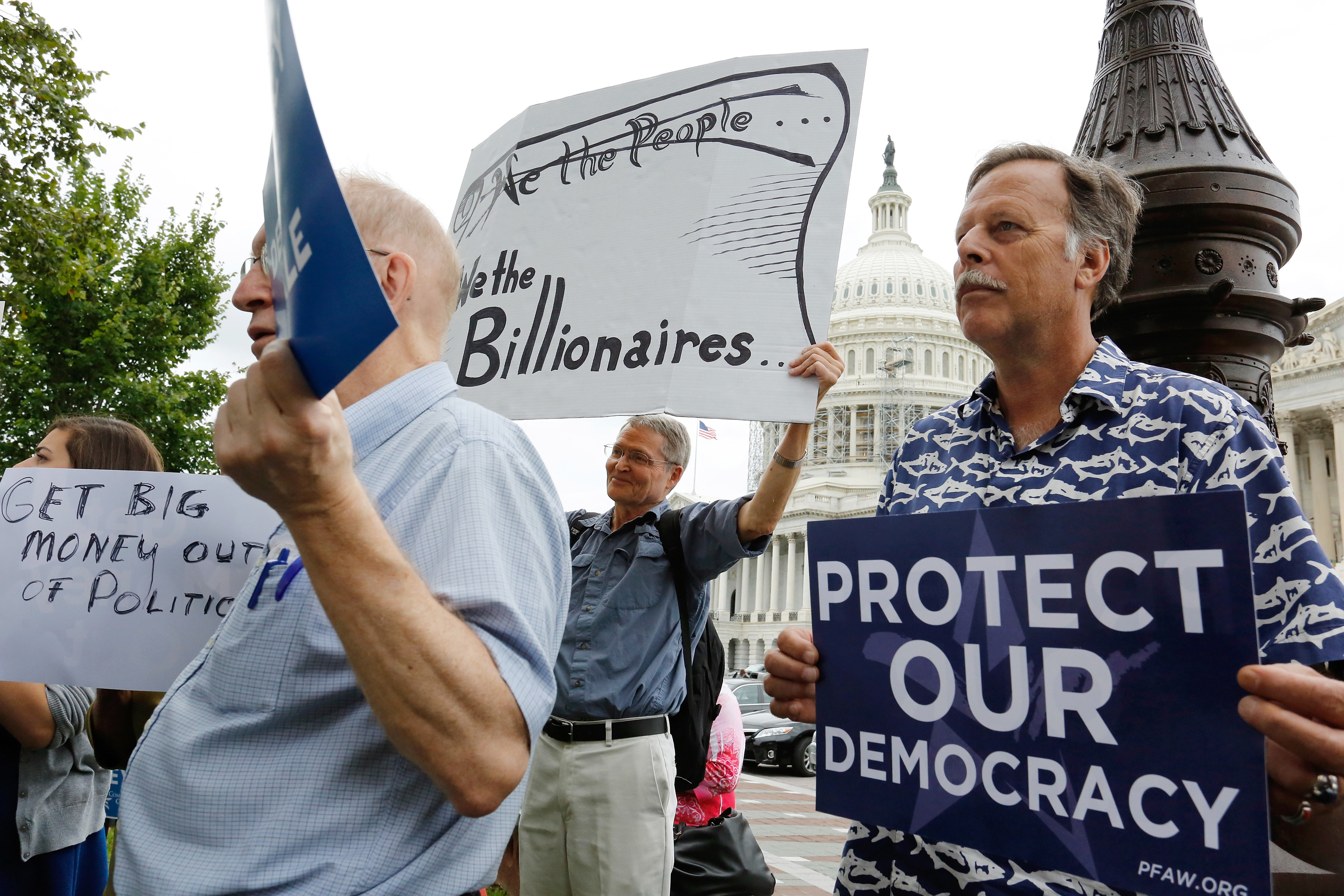 Supporters look on at a news conference on Capitol Hill led by Democratic senators and congressmen in support of a proposed constitutional amendment for campaign finance reform on September 8, 2014.