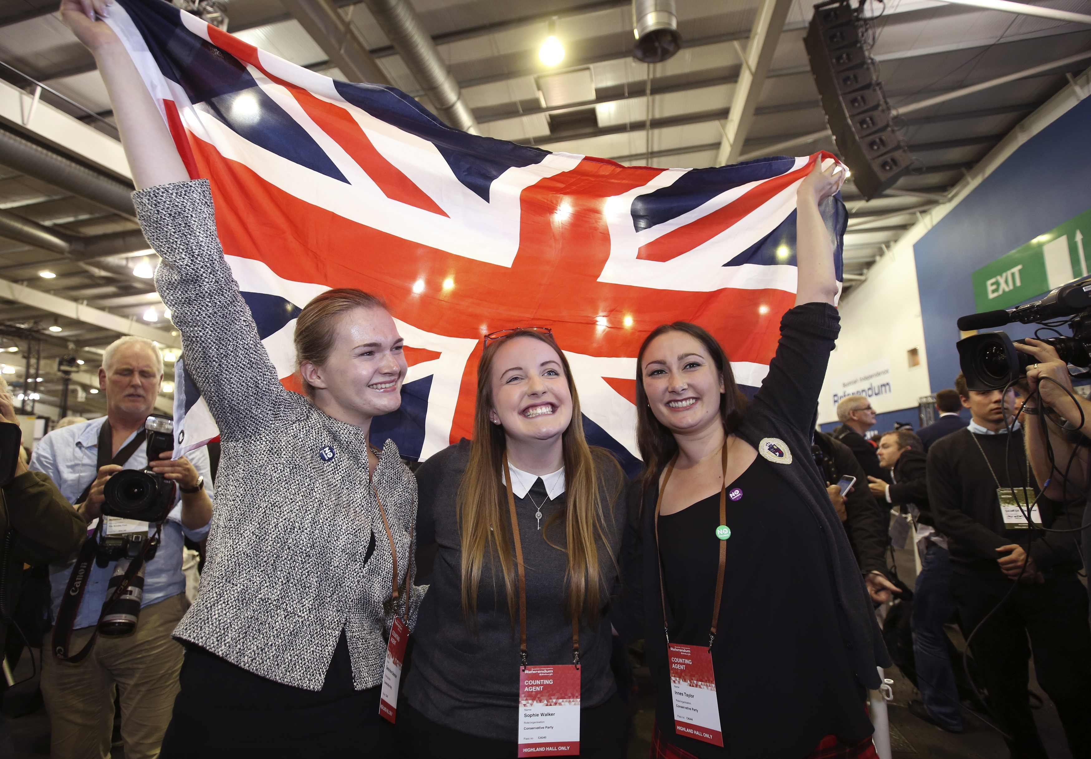 """Scottish supporters from the """"No"""" campaign celebrate as they hold up a Union flag in the city of Edinburgh."""
