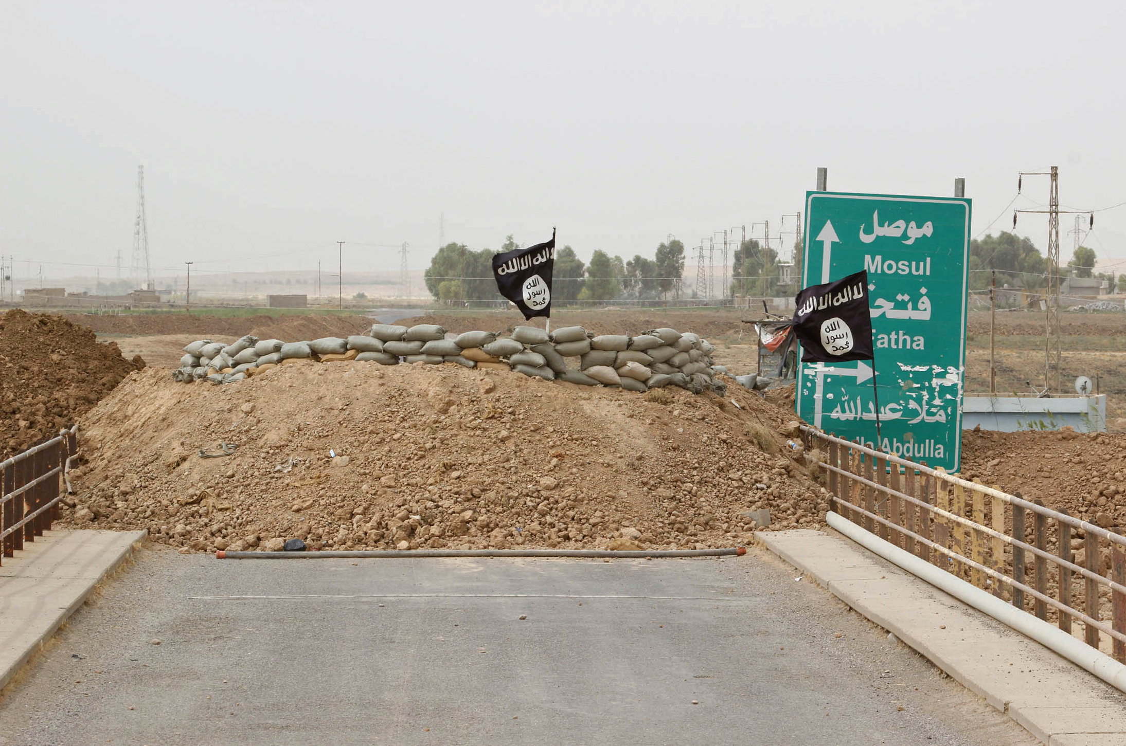 ISIS flags flutter on the Mullah Abdullah bridge in southern Kirkuk in early October 2014. The Iraqi Kurdish security forces are dug-in at the opposite end of the bridge.