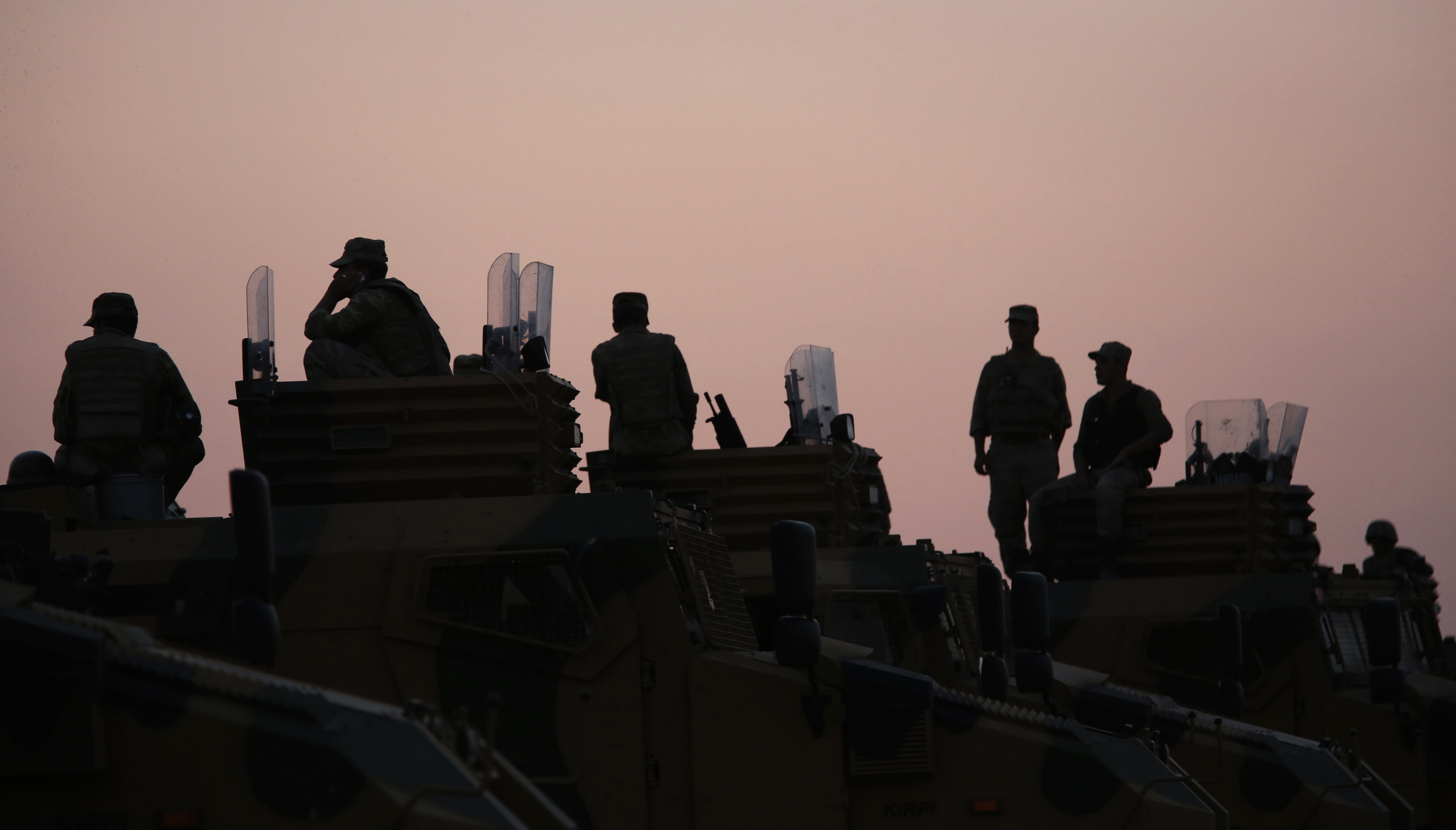 Turkish soldiers are silhouetted atop armoured vehicles near the Mursitpinar border crossing on the Turkish-Syrian border on October 3, 2014.