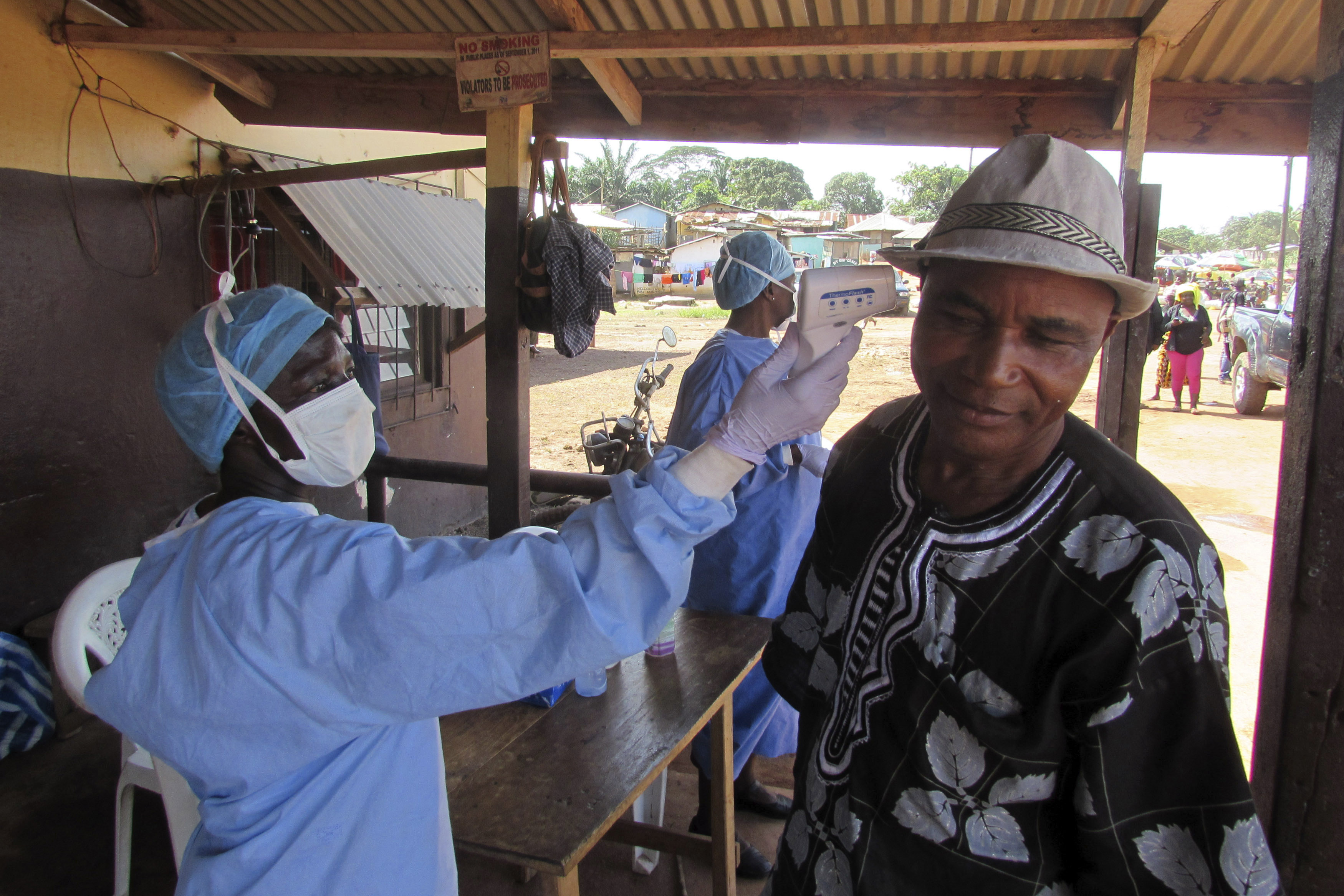 A health worker checks the temperature of a man at a roadside medical checkpoint outside Ganta, Liberia.