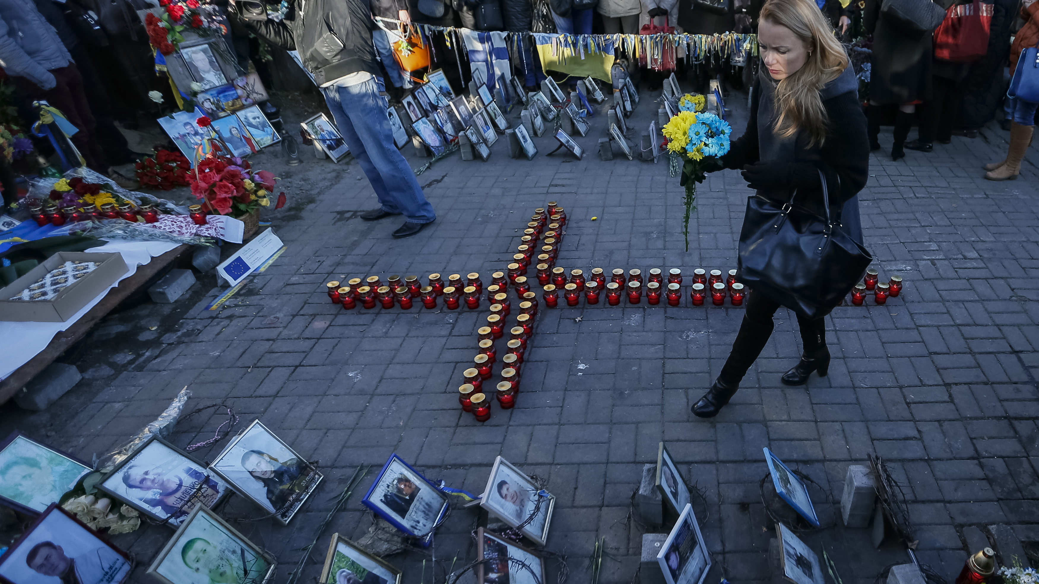 A woman walks near a memorial to those who died protesting against President Yanukovych, during a commemoration ceremony for them in Kiev Friday, as Ukrainians marked the first anniversary of protests which led to the revolution.